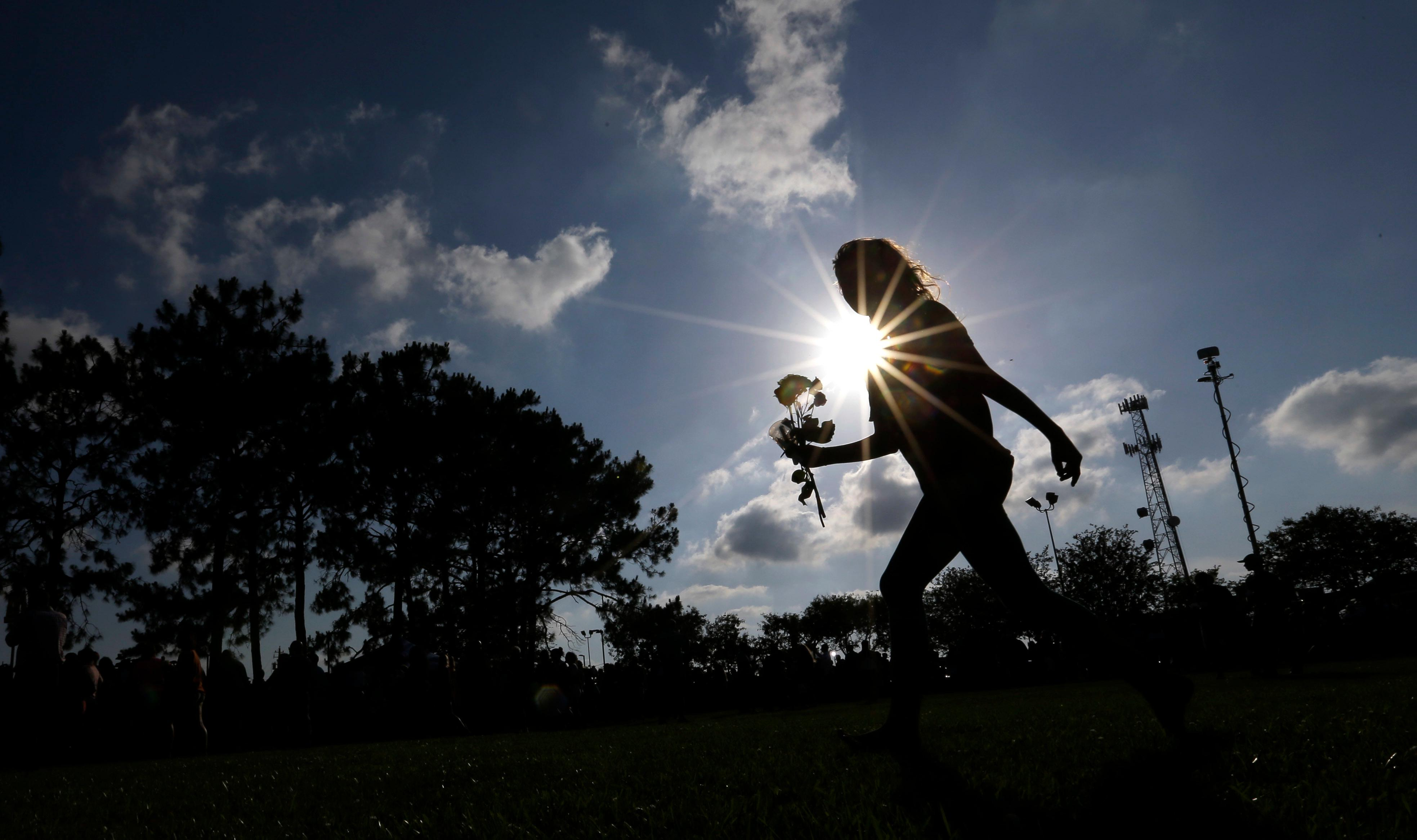 Hannah Harrison carries roses during a prayer vigil following a deadly shooting at Santa Fe High School in Santa Fe, Texas, on Friday, May 18, 2018. (AP Photo/David J. Phillip)