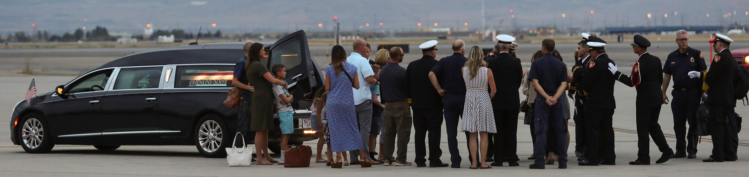 Members of the Draper City Fire Department and Unified Fire Authority Honor Guard stand with family members after the casket of Draper Battalion Chief Matt Burchett is placed in a hearse after being transported from California to Utah in a C130-J by the California Air National Guard. The C130-J landed at the Utah Air National Guard Base in Salt Lake City on Wednesday, Aug. 15, 2018. Burchett was killed while fighting the Mendocino Complex Fire north of San Francisco.
