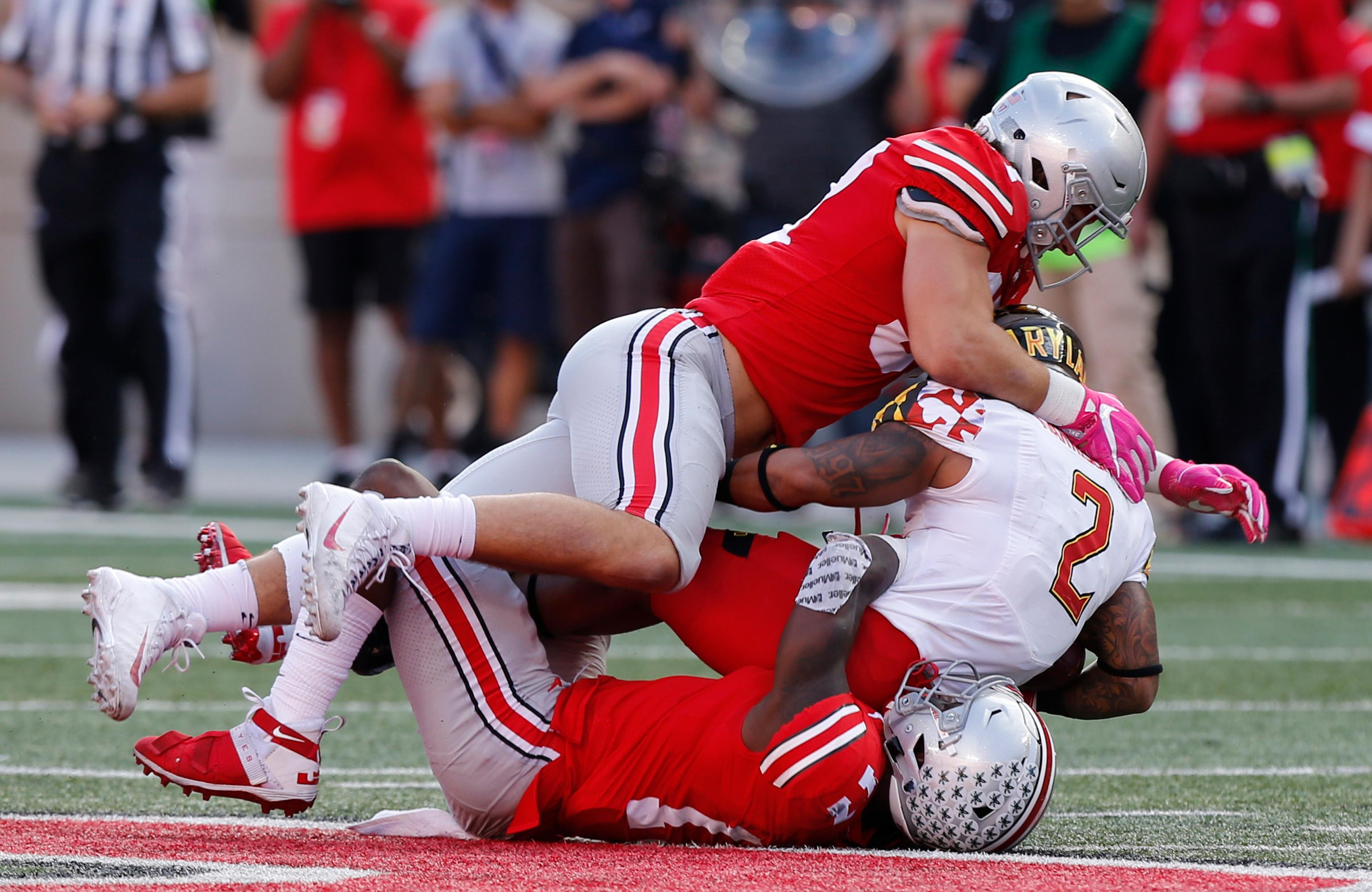 Ohio State defenders Nick Bosa, top, and Jerome Baker, bottom, tackle Maryland running back Lorenzo Harrison during the first half of an NCAA college football game Saturday, Oct. 7, 2017, in Columbus, Ohio. (AP Photo/Jay LaPrete)