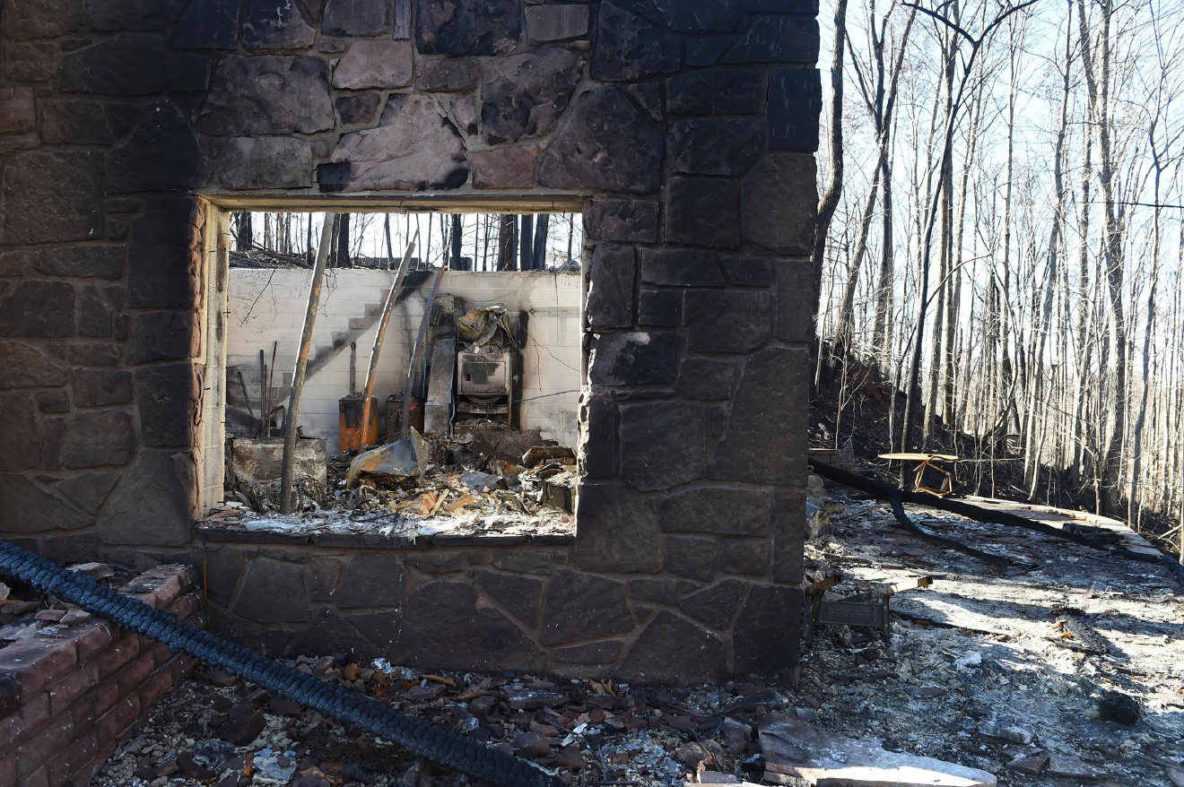 The charred foundation is all that remains of a home in the Cobbly Knob area of Pigeon Forge, Tenn., Thursday, Dec. 1, 2016. (Amy Smotherman Burgess/Knoxville News Sentinel via AP)