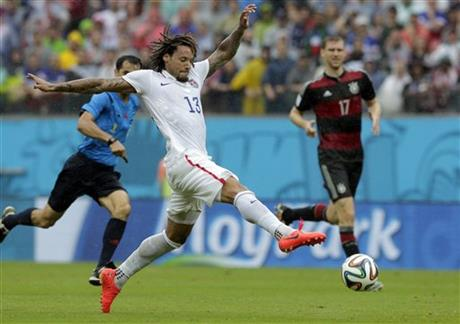 United States' Jermaine Jones goes with the ball as Germany's Per Mertesacker watches, at right, during the group G World Cup soccer match between the USA and Germany at the Arena Pernambuco in Recife, Brazil, Thursday, June 26, 2014.