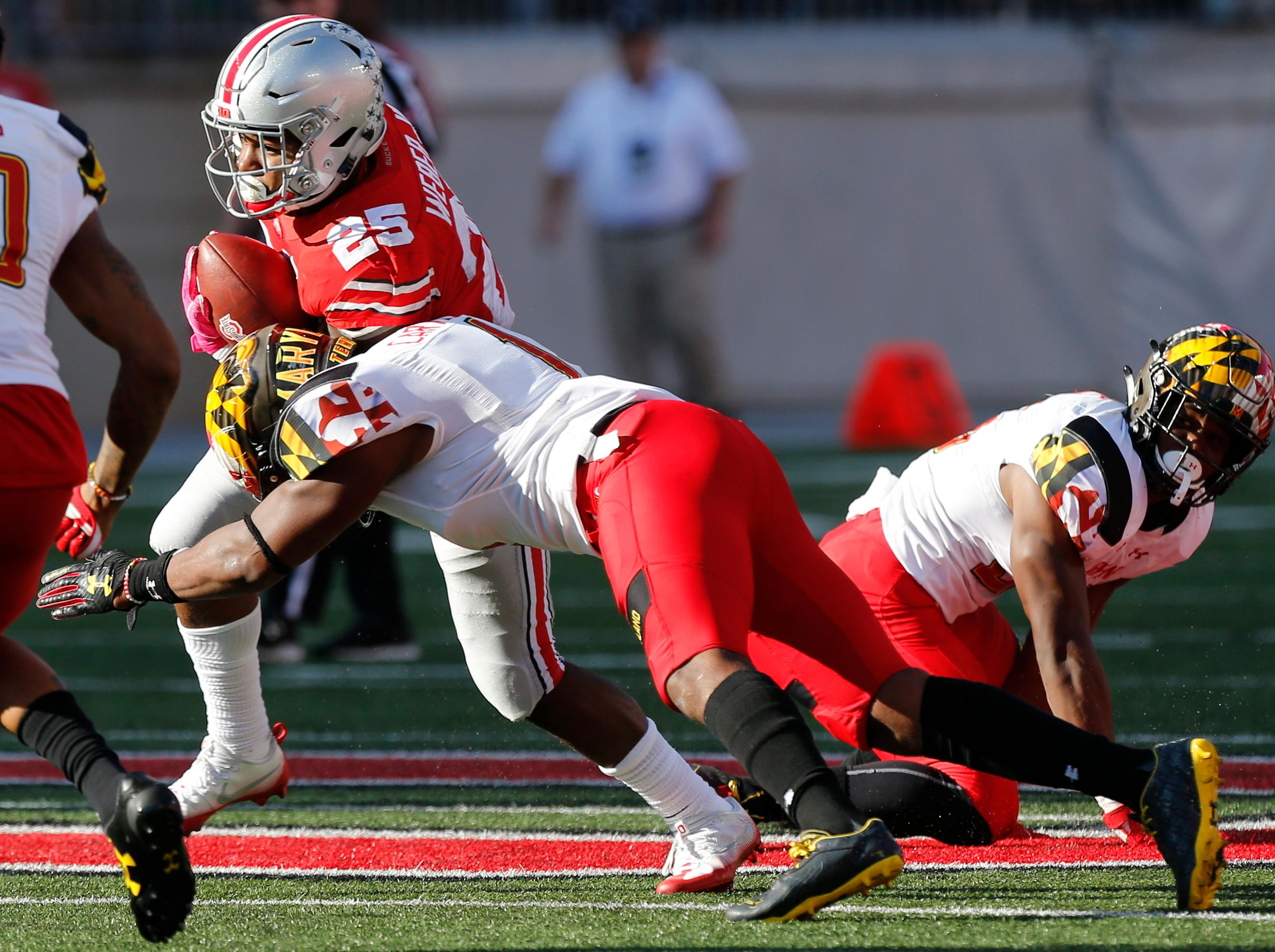 Ohio State running back Mike Weber, left, runs the ball against Maryland linebacker Jermaine Carter during the first half of an NCAA college football game Saturday, Oct. 7, 2017, in Columbus, Ohio. (AP Photo/Jay LaPrete)
