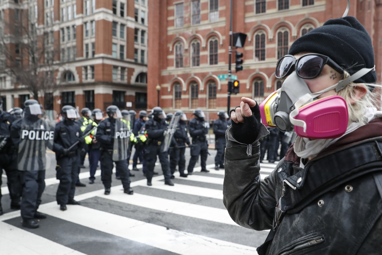 A protester faces off with a line of riot police during a demonstration after the inauguration of President Donald Trump, Friday, Jan. 20, 2017, in Washington. (AP Photo/John Minchillo)