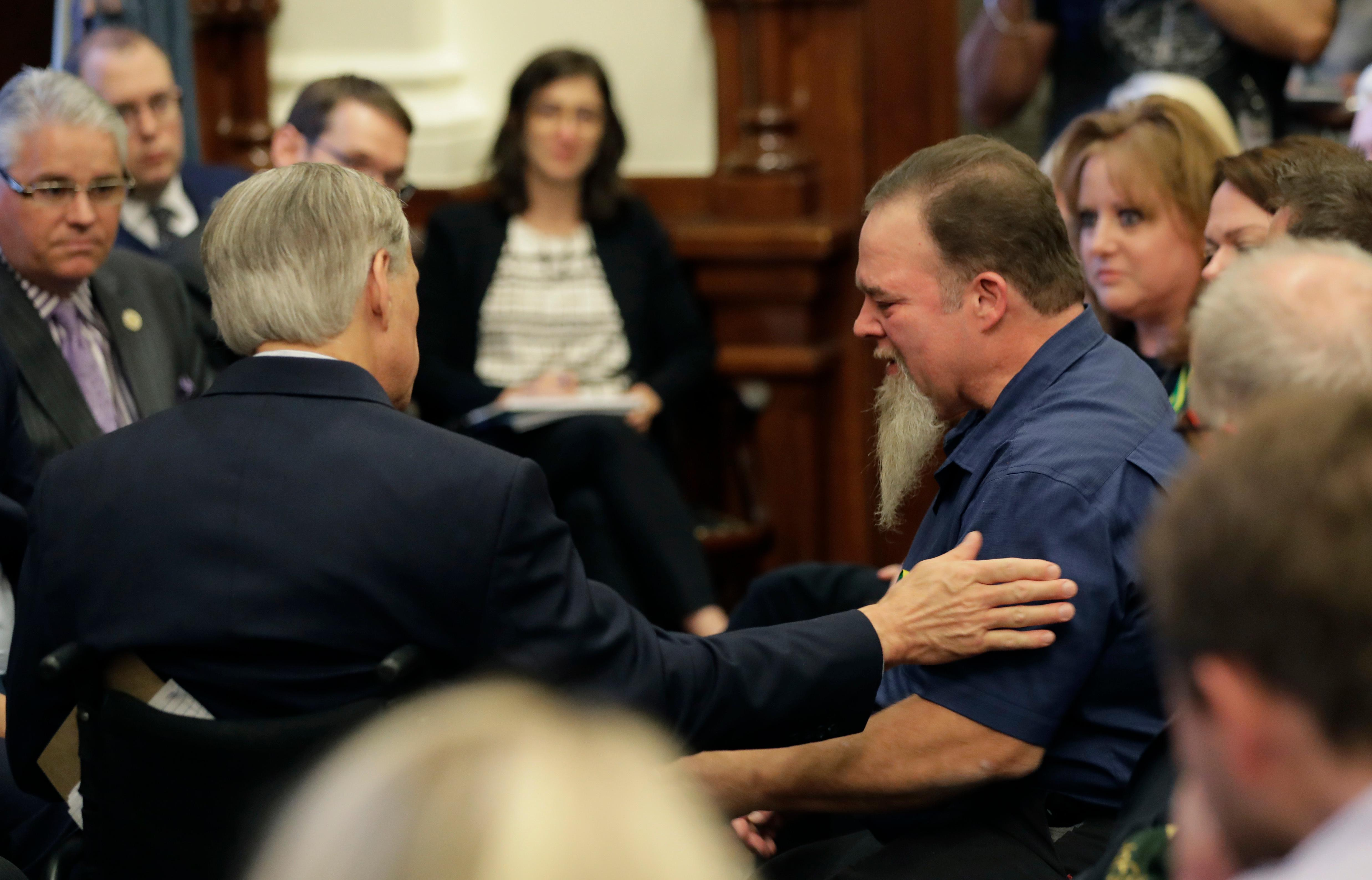 Texas Gov. Gregg Abbott, left, reached out to a man holding back tear as he speaks during a roundtable discussion in Austin, Texas, Thursday, May 24, 2018, to address safety and security at Texas schools in the wake of the shooting at Santa Fe, Texas. Thursday's roundtable included victims, students, families and educators from the Santa Fe, Alpine and Sutherland Springs communities. (AP Photo/Eric Gay)