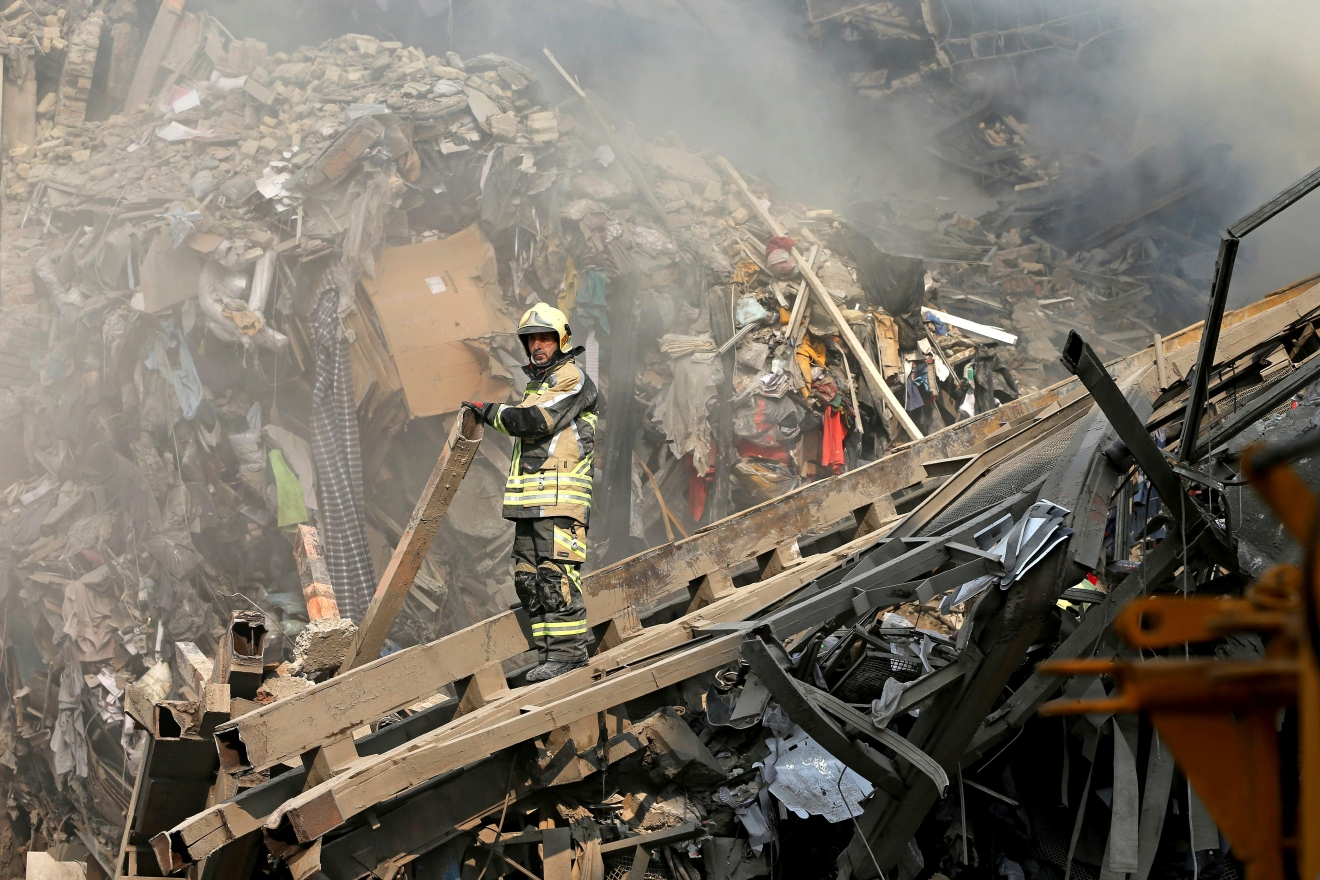 Iranian firefighters work at the scene of the collapsed Plasco building after being engulfed by a fire, in central Tehran, Iran, Thursday, Jan. 19, 2017. Iran's state-run Press TV says dozens of firefighters have been killed in the collapse of a burning high-rise building in Tehran. The collapse came just hours after the blaze erupted at the Plasco building, an iconic structure in central Tehran, just north of the capital's sprawling bazaar. Firefighters, soldiers and other emergency responders dug through the rubble, looking for survivors. (AP Photo/Ebrahim Noroozi)
