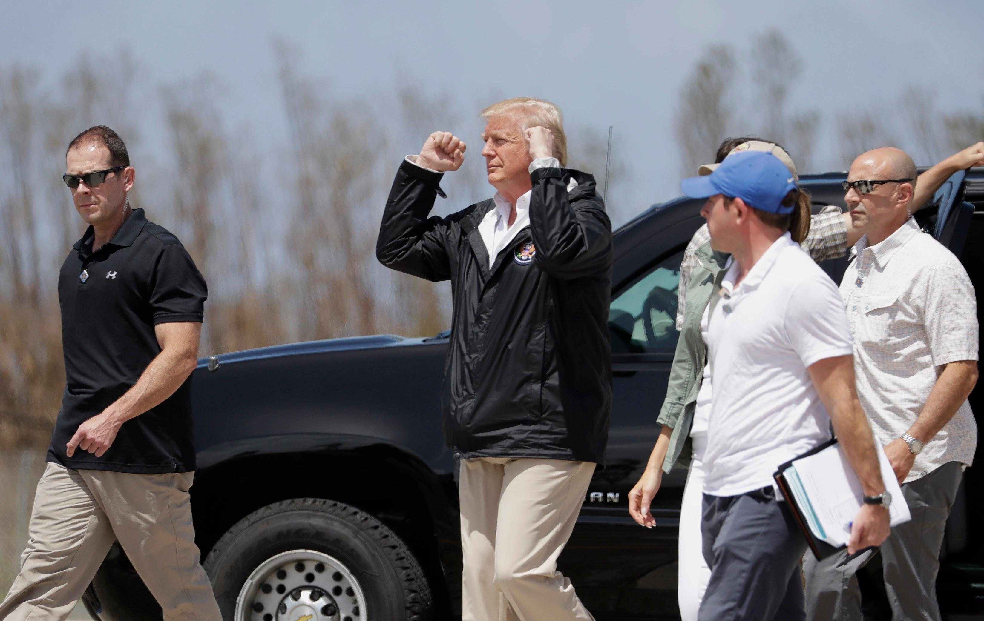 President Donald Trump gestures after arriving at the Luis Muñiz Air National Guard Base in San Juan, Puerto Rico, Tuesday, Oct. 3, 2017. Trump is visiting Puerto Rico in the wake of Hurricane Maria. (AP Photo/Evan Vucci)