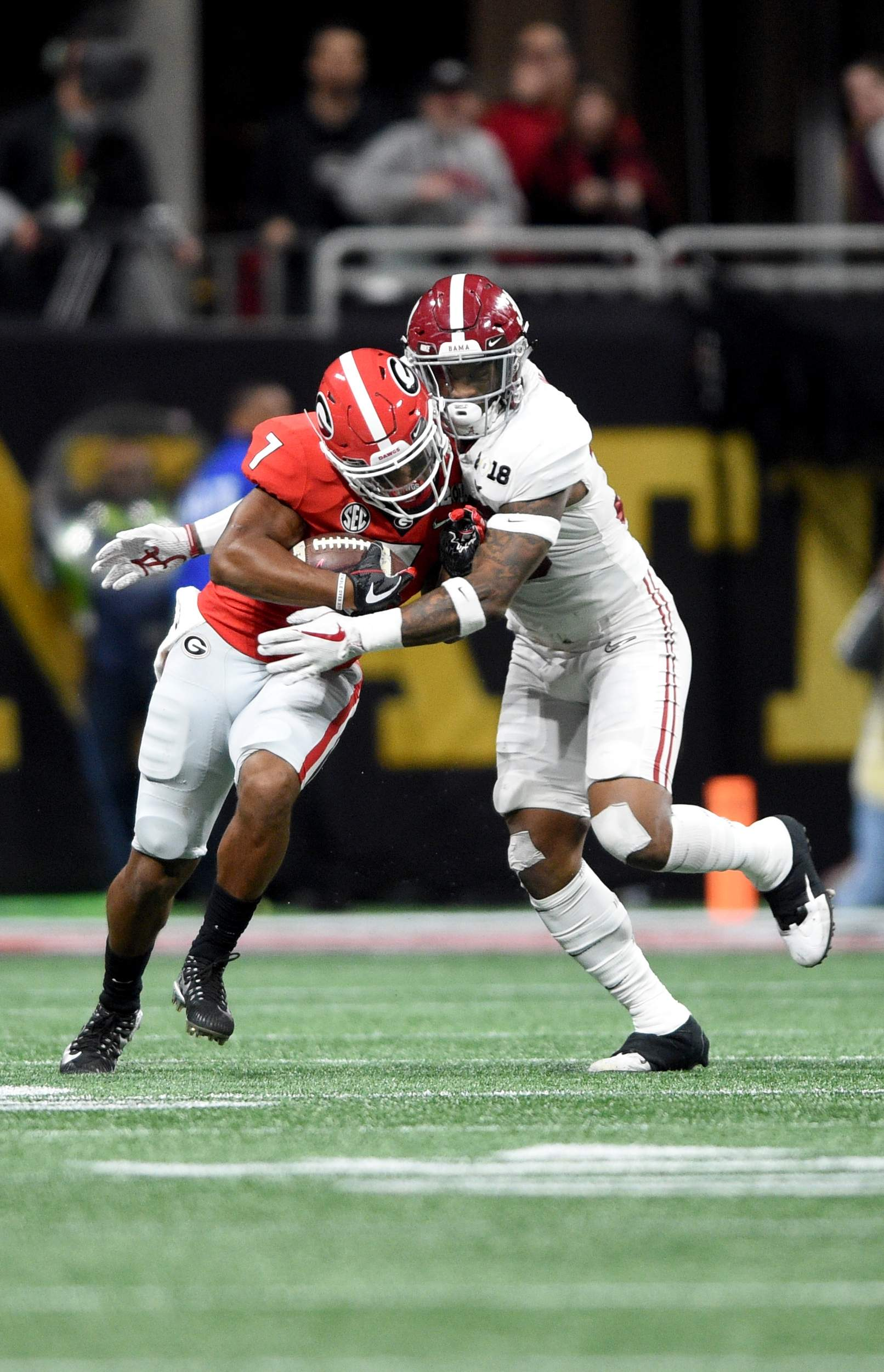 Georgia's D'Andre Swift, left, tries to break free of Alabama's Mack Wilson during the second period of the 2018 College Football Playoff National Championship at Mercedes-Benz Stadium in Atlanta, Ga., Monday evening January 8, 2018. MICHAEL HOLAHAN/AUGUSTA CHRONICLE