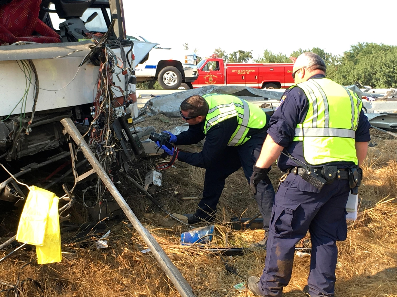 California Highway Patrol officers investigate the scene of a charter bus crash on northbound Highway 99 between Atwater and Livingston, Calif., Tuesday, Aug. 2, 2016. A charter bus veered off a central California freeway before dawn Tuesday and struck a pole that sliced the vehicle nearly in half, killing multiple people and sending at least five others to hospitals, authorities said. (AP Photo/Scott Smith)
