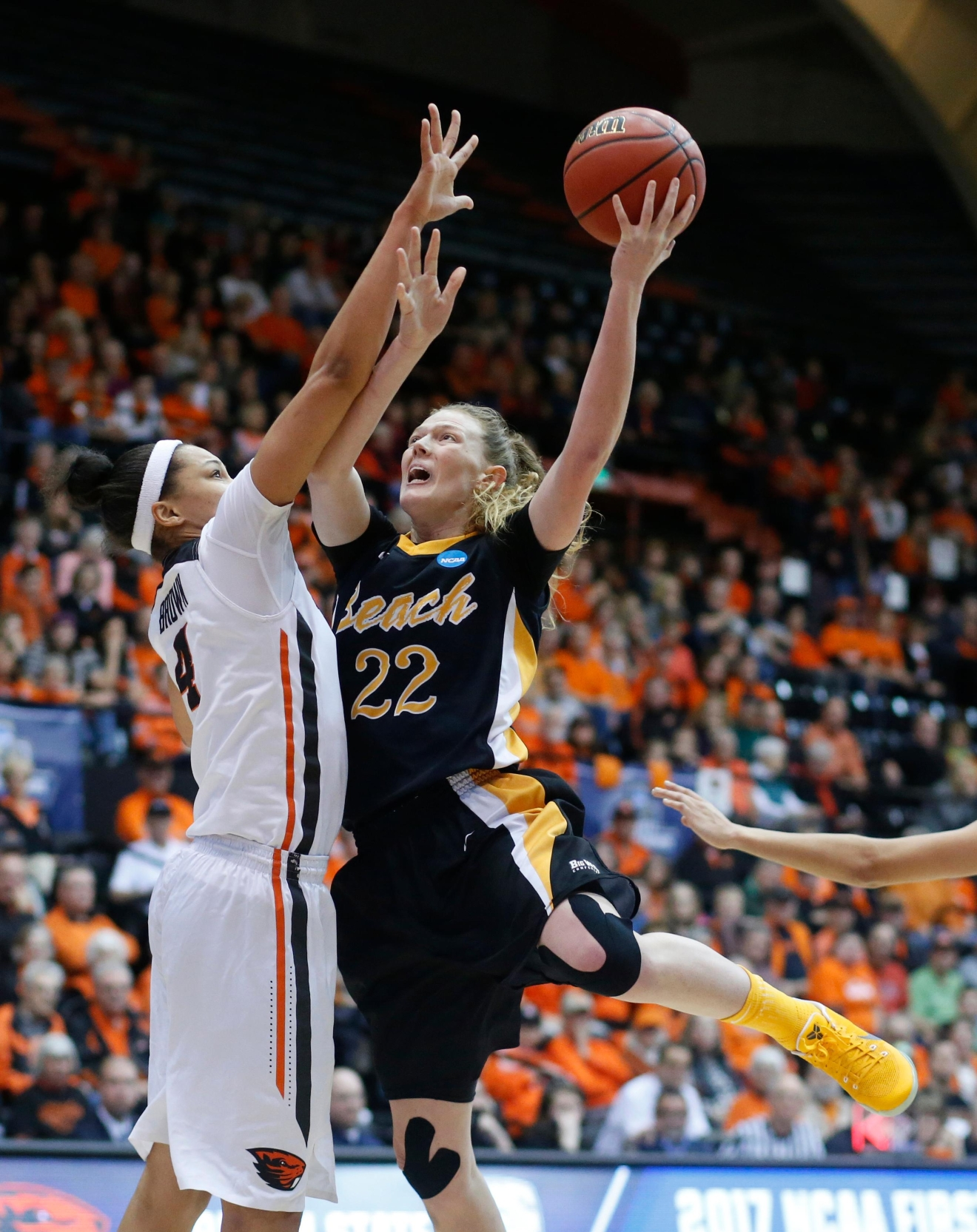 Long Beach State's Madison Montgomery (22) shoots past Oregon State's Breanna Brown during the first half in a first-round game in the women's NCAA college basketball tournament Friday, March 17, 2017, in Corvallis, Ore. (AP Photo/Timothy J. Gonzalez)