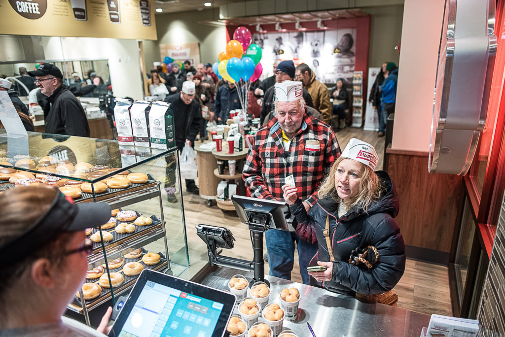 "Debbie Koch and Gerry Albert order their doughnuts during the opening of the Auburn Krispy Kreme store Monday morning. The two were up early in the morning waiting for the store to open. Albert ended up getting one of the 'golden tickets"" in his box of donuts, which will get him a dozen free doughnuts a month for a year. (Andree Kehn/Sun Journal)"