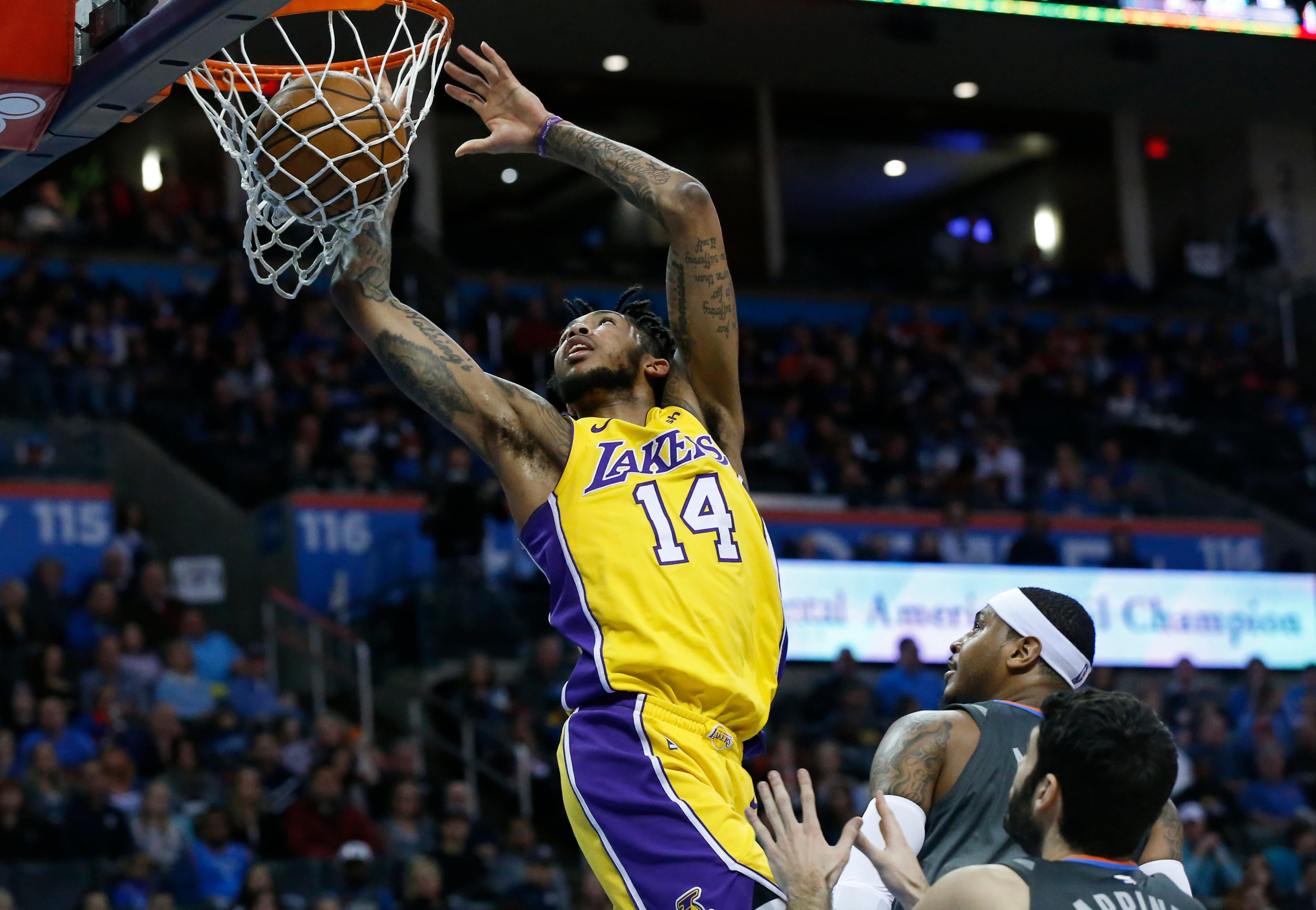 Los Angeles Lakers forward Brandon Ingram (14) dunks in front of Oklahoma City Thunder forward Carmelo Anthony, center, and guard Alex Abrines, right, in the first half of an NBA basketball game in Oklahoma City, Sunday, Feb. 4, 2018. (AP Photo/Sue Ogrocki)