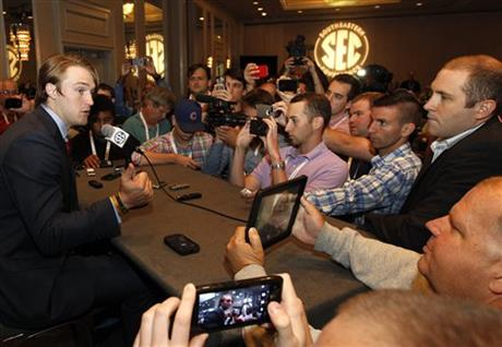 Mississippi quarterback Bo Wallace, left, speaks to the media at the Southeastern Conference NCAA college football media days, Thursday, July 17, 2014, in Hoover, Ala.