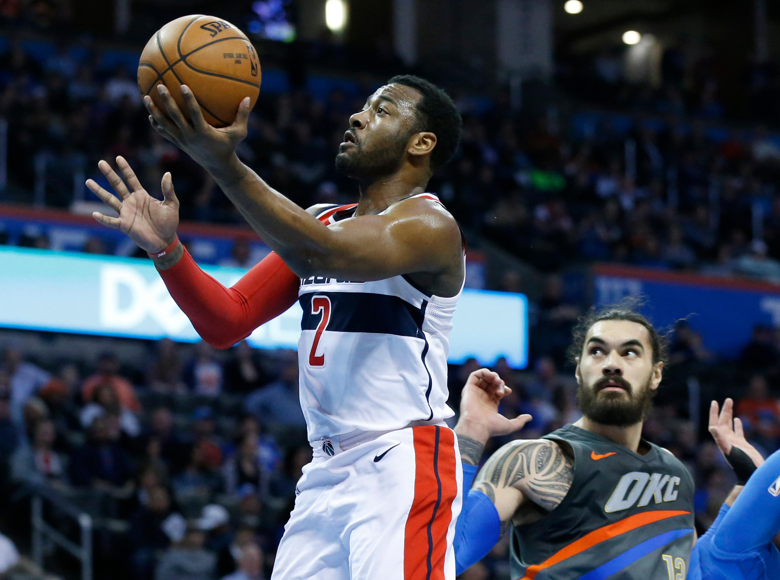 Washington Wizards guard John Wall (2) moves past Oklahoma City Thunder center Steven Adams, right, to shoot during the second quarter of an NBA basketball game in Oklahoma City, Thursday, Jan. 25, 2018. (AP Photo/Sue Ogrocki)