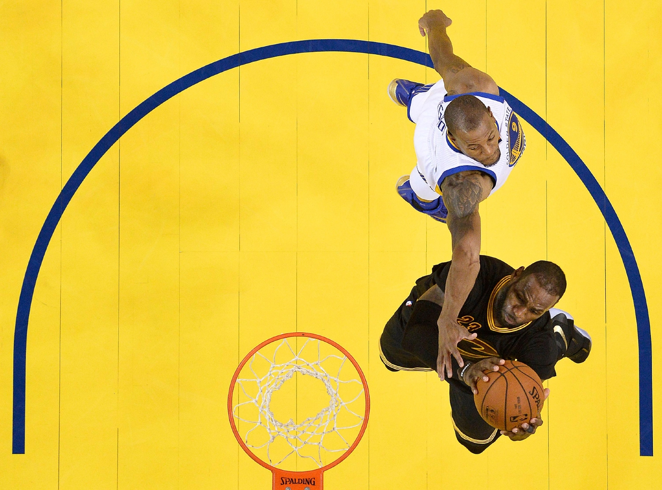 Cleveland Cavaliers forward LeBron James, bottom, shoots against Golden State Warriors forward Andre Iguodala during the second half of Game 7 of basketball's NBA Finals in Oakland, Calif., Sunday, June 19, 2016. The Cavaliers won 93-89. (John G. Mabanglo, European Pressphoto Agency via AP, Pool)