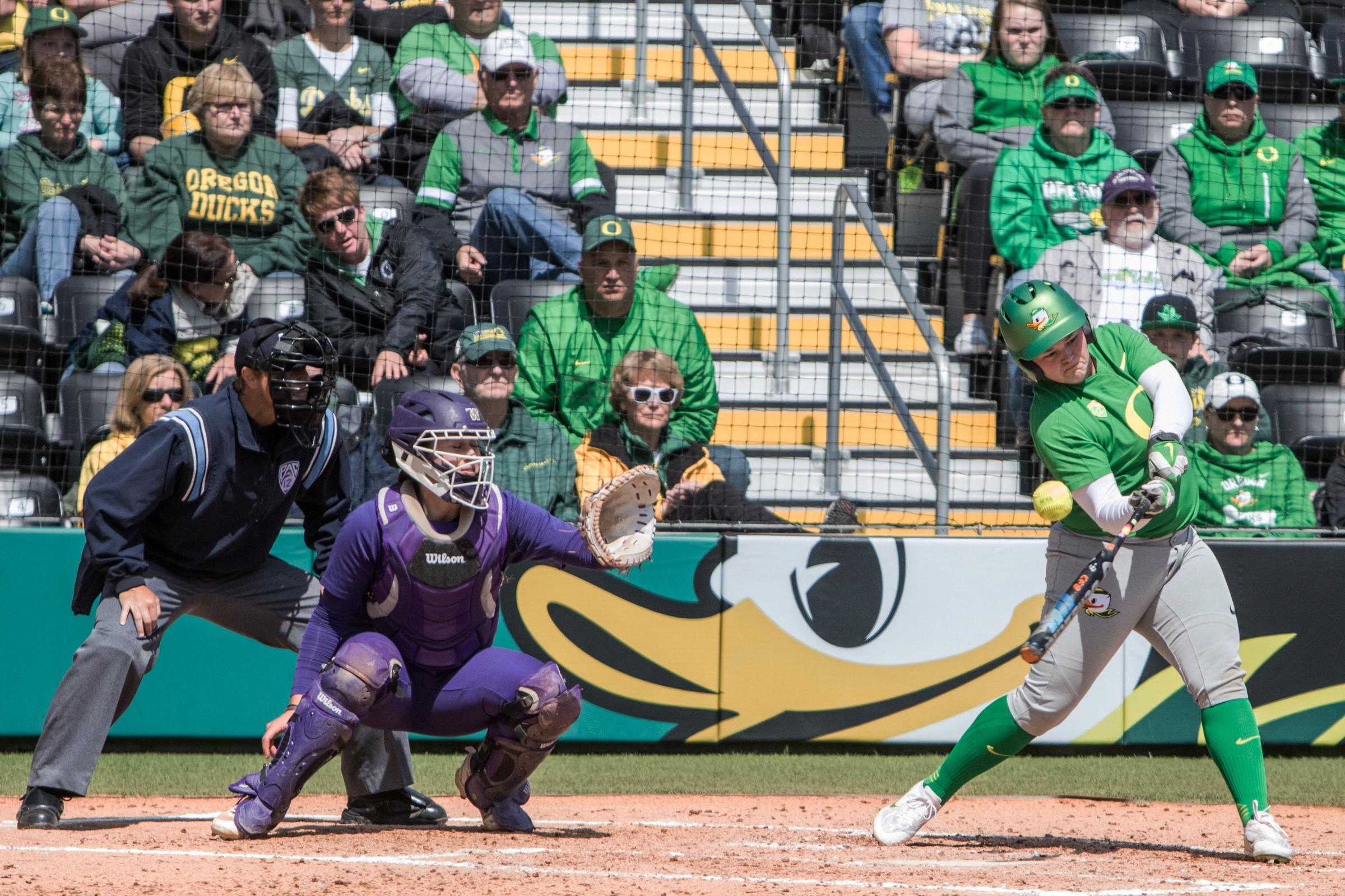 Oregon Ducks infielder Madi Bishop (#23) swings low on a pitch. In the final game of a three-game series, the University of Washington Huskies defeated the Oregon Ducks 5-3.  The Ducks led through the bottom of the 7th inning, but Washington's Morganne Flores (#47) tied it up with a two-run double.  Flores drove in two more runs in the 9th to take the lead.  Photo by Austin Hicks, Oregon News Lab