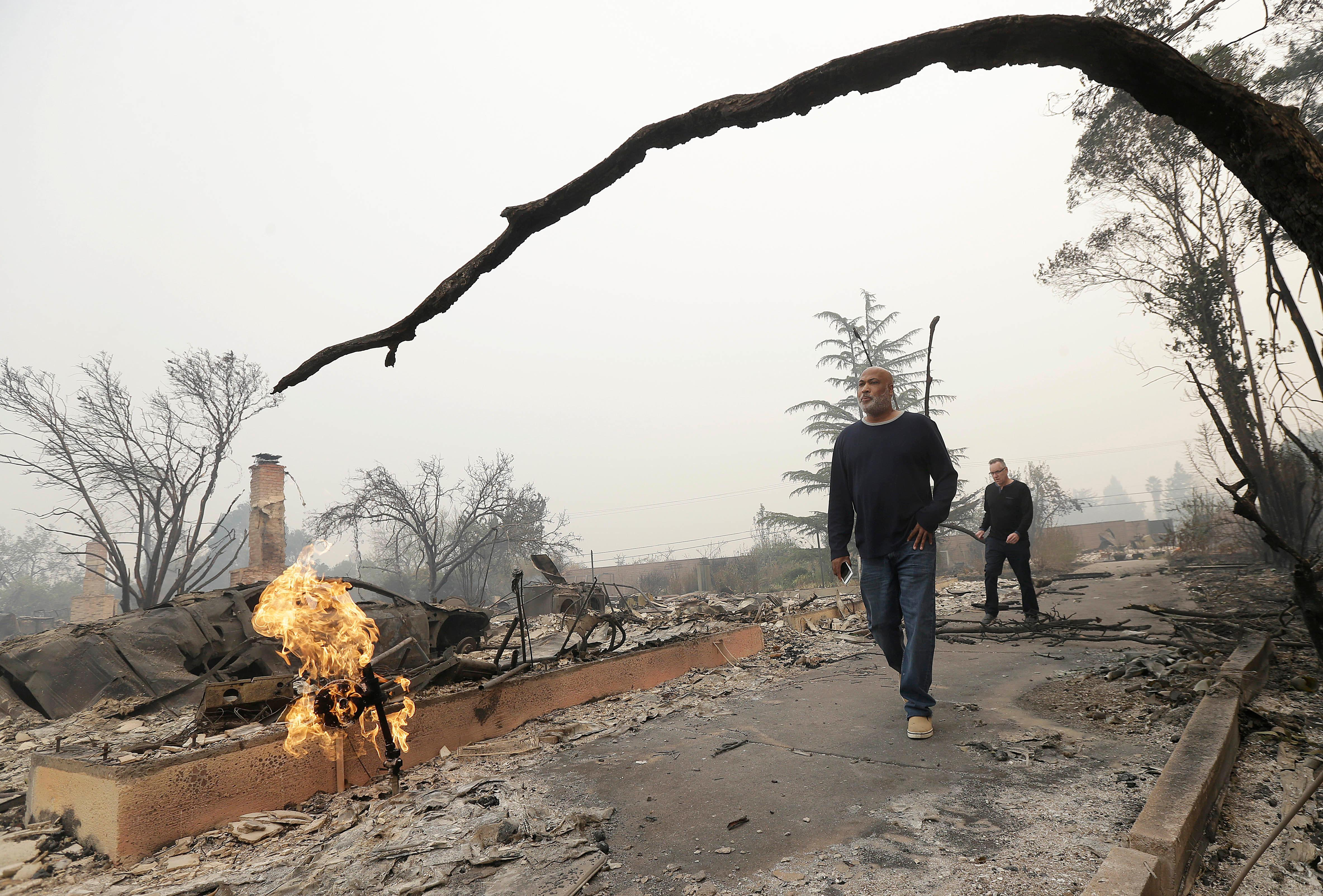 Darrel Spain, center, and his husband Mark Papale walk along a path where their house was destroyed from fires as they look for their missing cat in Kenwood, Calif., Tuesday, Oct. 10, 2017. (AP Photo/Jeff Chiu)