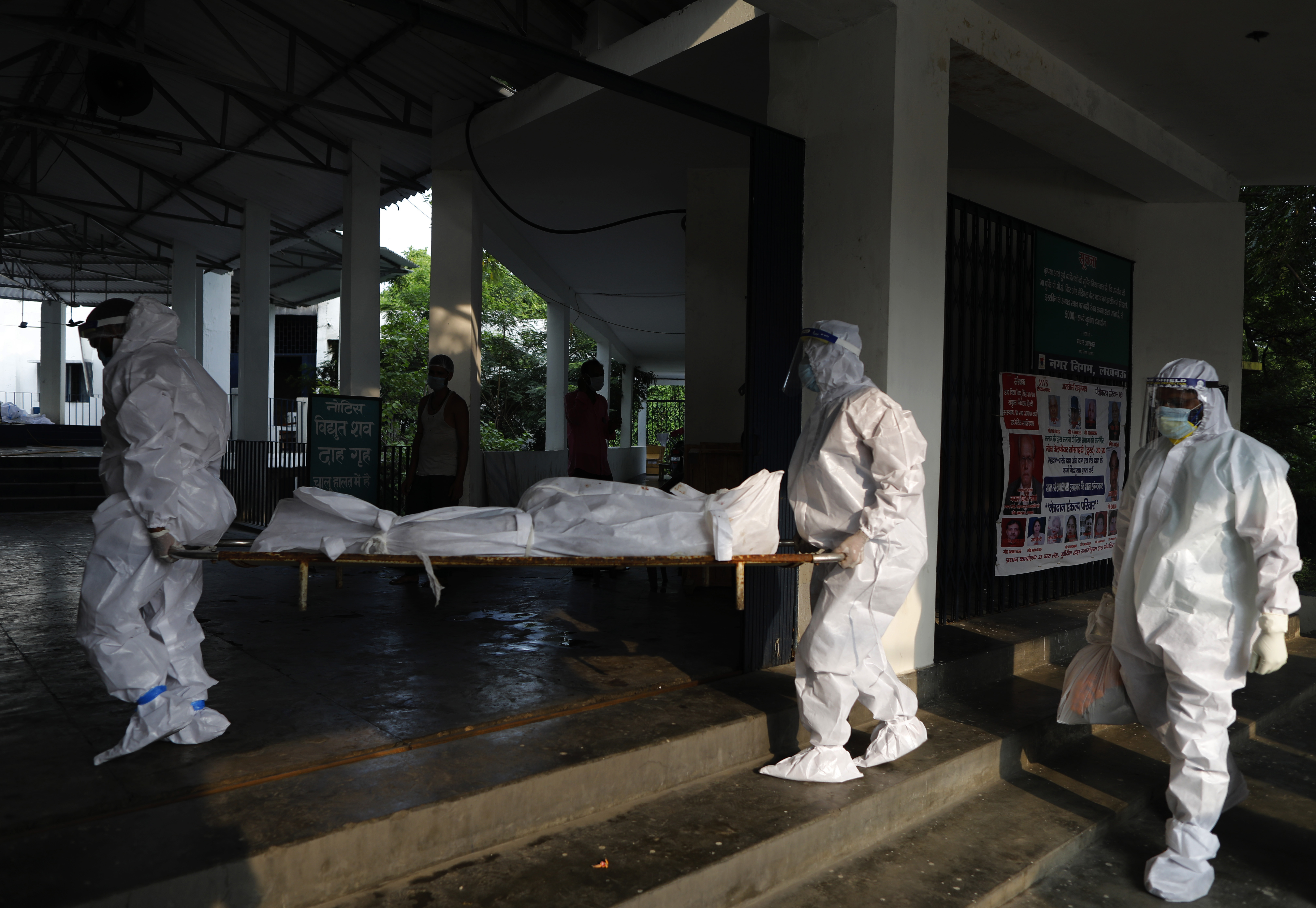 Health workers wearing personnel protection equipment carry the body of a COVID-19 victim for cremation in Lucknow, India, Saturday, Sept. 12, 2020. India's coronavirus cases are now the second-highest in the world and only behind the United States. (AP Photo/Rajesh Kumar Singh)