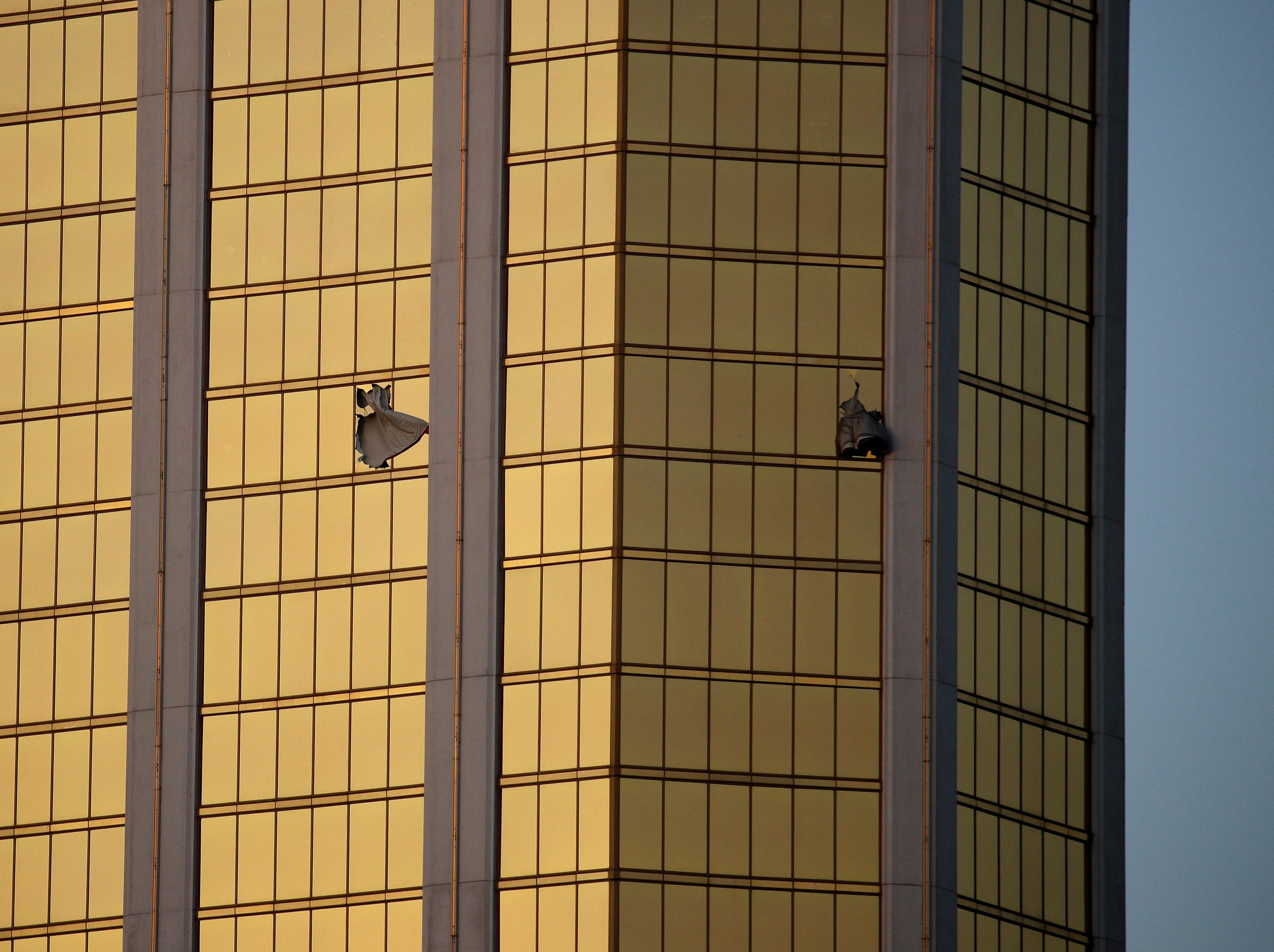 Drapes billow out of broken windows at the Mandalay Bay resort and casino Monday, Oct. 2, 2017, on the Las Vegas Strip following a mass shooting at a music festival in Las Vegas. Authorities say Stephen Craig Paddock broke the windows and began firing with a cache of weapons, killing dozens and injuring hundreds. (AP Photo/John Locher)