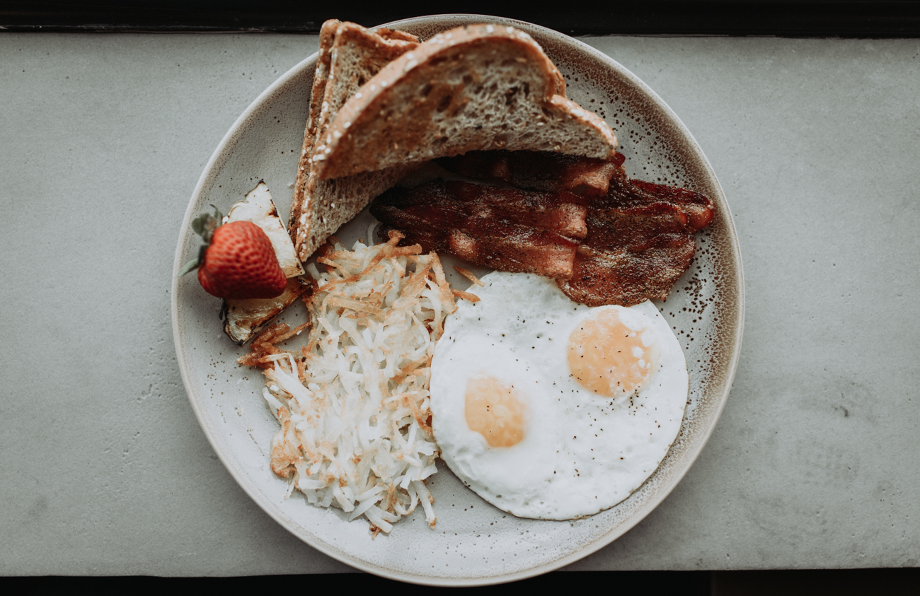 Traditional breakfast with two eggs, hash browns, multigrain toast and bacon / Image: Brianna Long // Published: 5.17.18
