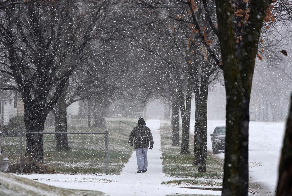 A man walks during a snow storm on Friday, Nov. 18, 2016 in St. Cloud, Minn.  The National Weather Service has issued a blizzard warning for Friday in eastern parts of North and South Dakota and  Minnesota, as well as winter storm warnings for other parts of those states and Nebraska. (Dave Schwarz/St. Cloud Times via AP)
