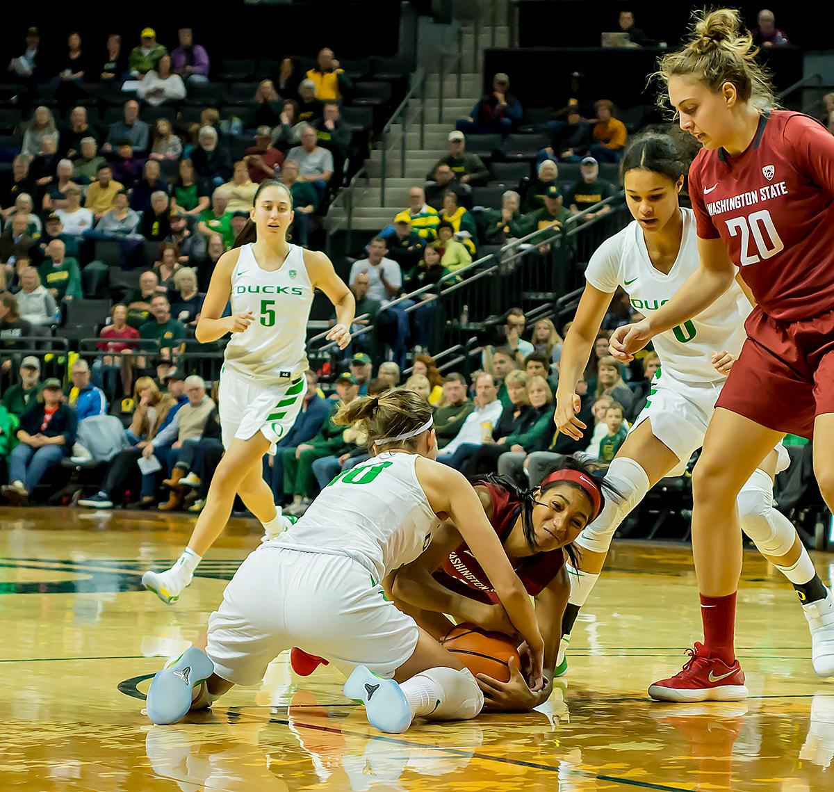 Oregon Ducks Lexi Bando (#10) fights for possession of the ball with Washington State University Cougars Caila Hailey (#1). In their first conference basketball game of the season, the Oregon Women Ducks defeated the Washington State Cougars 89-56 in Matt Knight Arena Saturday afternoon. Oregon's Ruthy Hebard ran up 25 points with 10 rebounds. Sabrina Ionescu shot 25 points with five three-pointers and three rebounds. Lexi Bando added 18 points, with four three-pointers and pulled down three rebounds. Satou Sabally ended the game with 14 points with one three-pointer and two rebounds. The Ducks are now 12-2 overall with 1-0 in conference and the Cougars stand at 7-6 overall and 0-1 in conference play. The Oregon Women Ducks next play the University of Washington Huskies at 1:00 pm on Sunday. Photo by Karly DeWees, Oregon News Lab