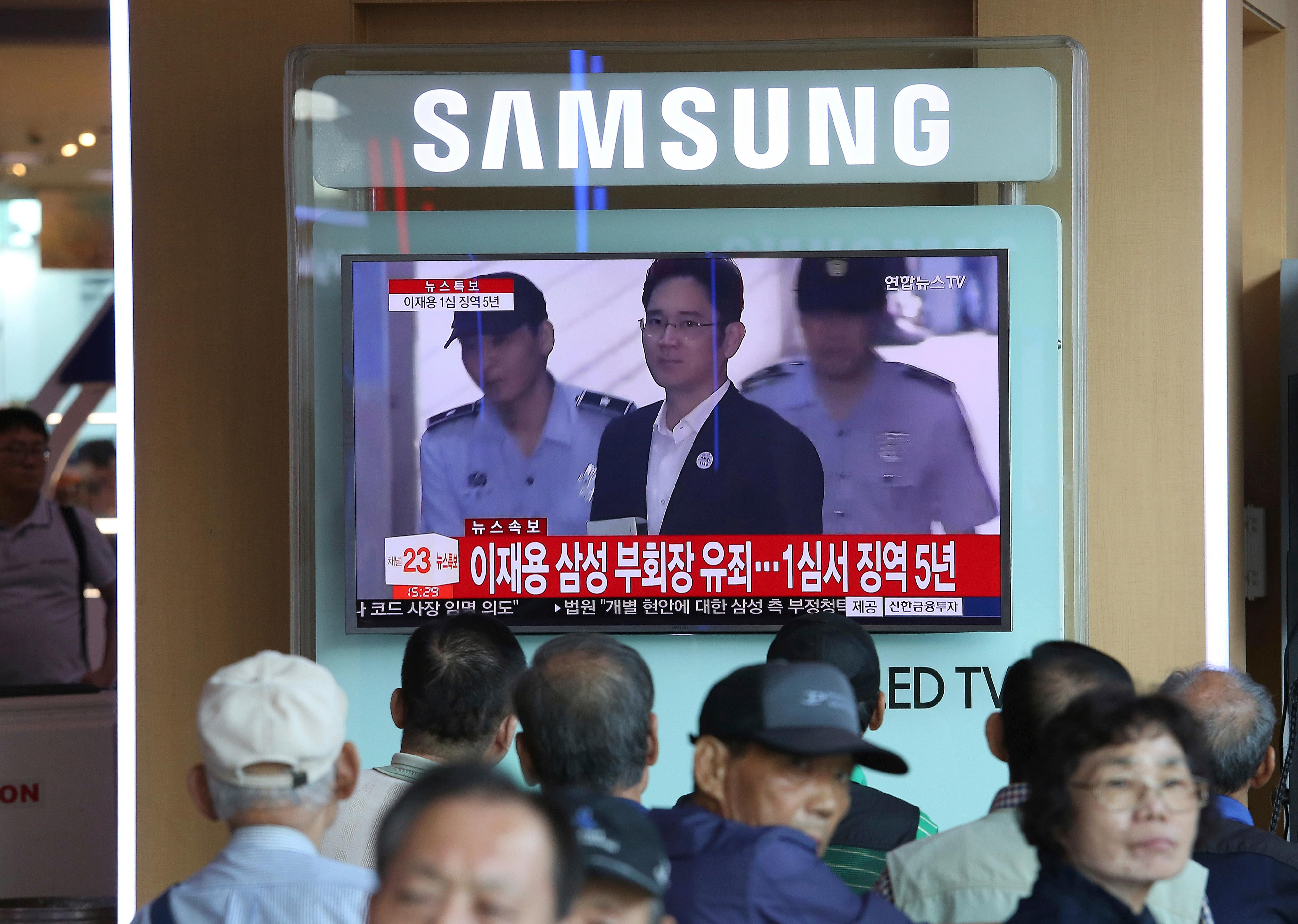"People watch a TV screen showing Samsung Electronics Co. Vice Chairman Lee Jae-yong's arrival for his trail at the Seoul Central District Court, at the Seoul Railway Station in Seoul, South Korea, Friday, Aug. 25, 2017. The court has sentenced the billionaire Samsung heir to five years in prison for bribery and other crimes that fed public anger leading to the ouster of Park Geun-hye as South Korea's president. The Korean letters read: ""Court sentenced Samsung Electronics Vice Chairman Lee Jae-yong to five years in prison."" (AP Photo/Ahn Young-joon)"