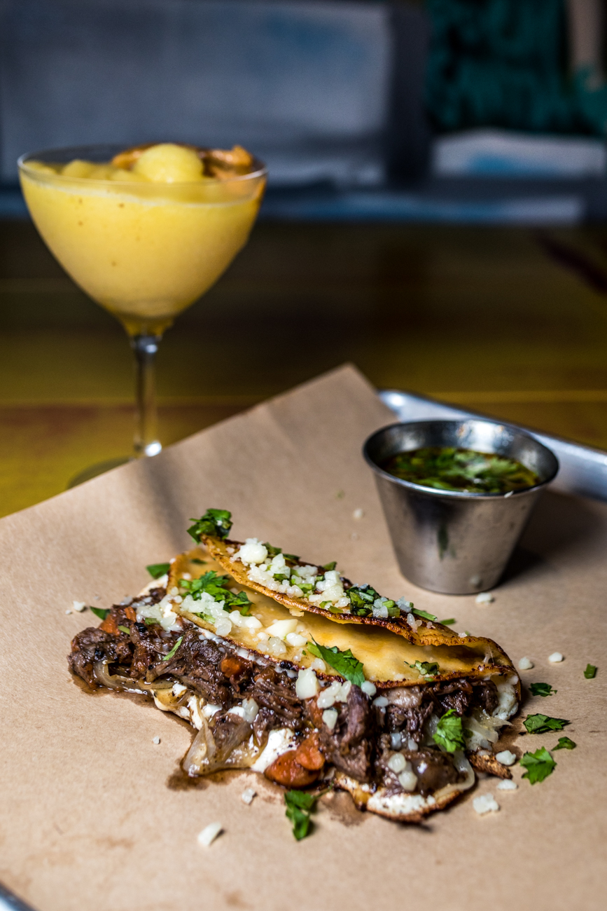 Birria Taco Jugoso: Papi's slow roasted beef, grilled onions, queso oaxaca, cotija, chile de arbol, salsa, cilantro, sour cream, pico, and Birria dipping sauce / Image: Catherine Viox // Published: 8.24.20
