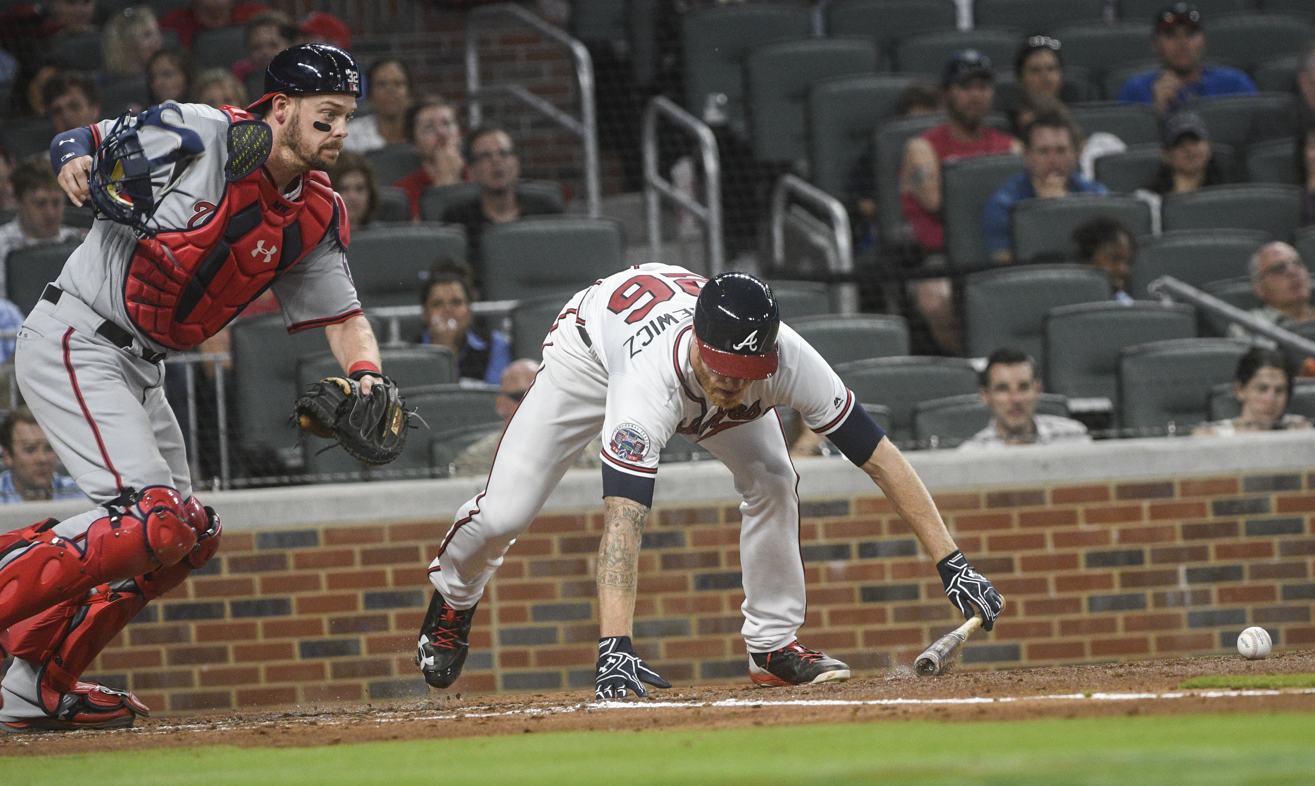 Atlanta Braves' Mike Foltynewicz loses his balance after laying down a bunt, as Washington Nationals catcher Matt Wieters chases the ball during the third inning of a baseball game, Tuesday, April 18, 2017, in Atlanta. Foltynewicz was out at first. (AP Photo/John Amis)