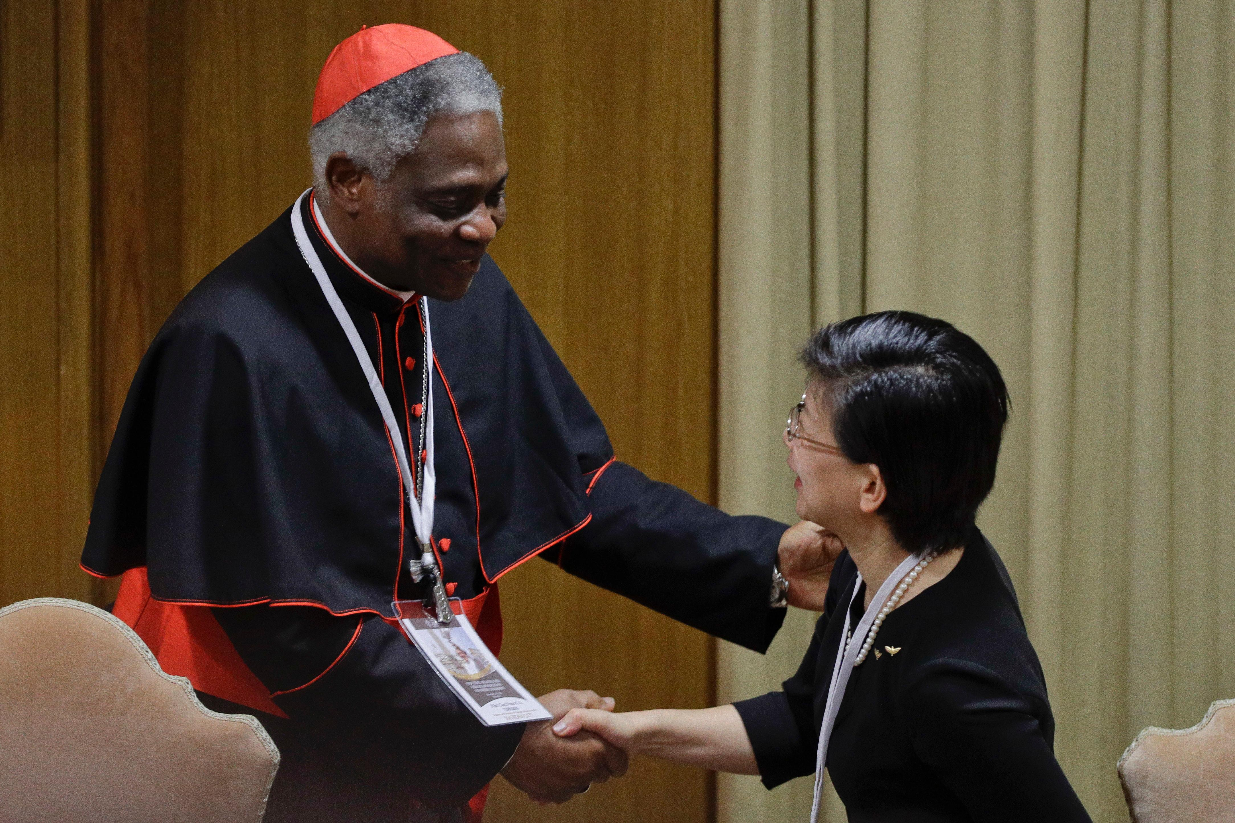 Cardinal Peter Kodwo Appiah Turkson, left, shakes hands with U.N. high representative for disarmament affairs Izumi Nakamitsu, during a conference on nuclear disarmament, at the Vatican, Friday, Nov. 10, 2017. The Vatican hosted Nobel laureates, U.N. and NATO officials and a handful of nuclear powers at a conference aimed at galvanizing support for a global shift from the Cold War era policy of nuclear deterrence to one of total nuclear disarmament.(AP Photo/Andrew Medichini)