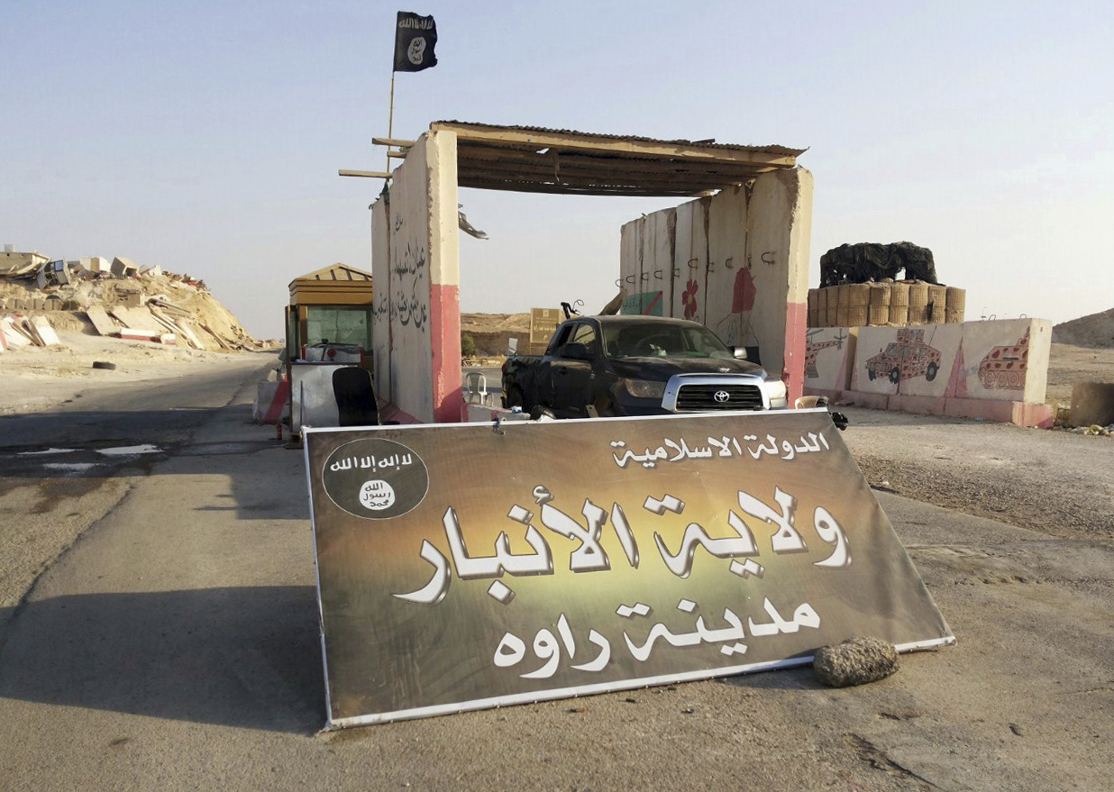 "FILE - In thisFILE - In this Tuesday, July 22, 2014, file photo, a sign is posted at a checkpoint belonging to the Islamic State group, captured from the Iraqi Army, at the main entrance of Rawah, 175 miles (281 kilometers) northwest of Baghdad, Iraq. Arabic reads, ""Islamic State, the Emirate of Anbar, City of Rawah."" Iraq's Defense Ministry said Friday, Nov. 17, 2017 Iraqi forces have retaken the last IS-held town in the country, more than three years after the militant group stormed nearly a third of Iraqi territory.(AP Photo, File)"