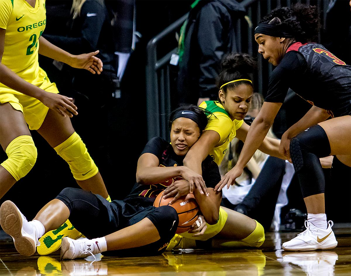 The Trojan's Sadie Edwards (#14) and the Duck's Justine Hall (#3) fight for the ball. The Oregon Ducks defeated the USC Trojans 80-74 on Friday at Matthew Knight Arena in a  game that went into double overtime. Lexi Bando sealed the Ducks victory by scoring a three-pointer in the closing of the game. Ruthy Hebard set a new NCAA record of 30 consecutive field goals, the old record being 28. Ruthy Hebard got a double-double with 27 points and 10 rebounds, Mallory McGwire also had 10 rebounds. The ducks had four players in double digits. The Ducks are now 24-4, 13-2 in the Pac-12, and are tied for first with Stanford. Photo by August Frank, Oregon News Lab