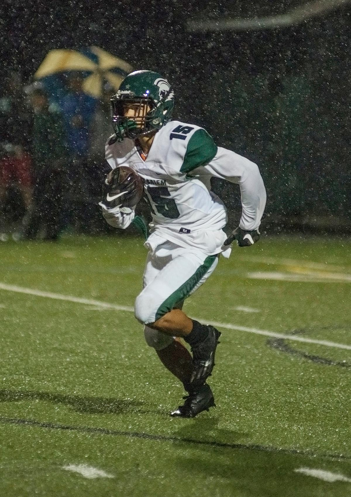 West Salem Titans wide receiver Anthony Gould carries the ball down field.  On a rainy Monday evening, Sheldon defeated West Salem 41 to 7 at their home field. The game had been postponed from Friday due to unhealthy levels of smoke in the atmosphere from nearby forest fires. Abigail Winn, Oregon News Lab
