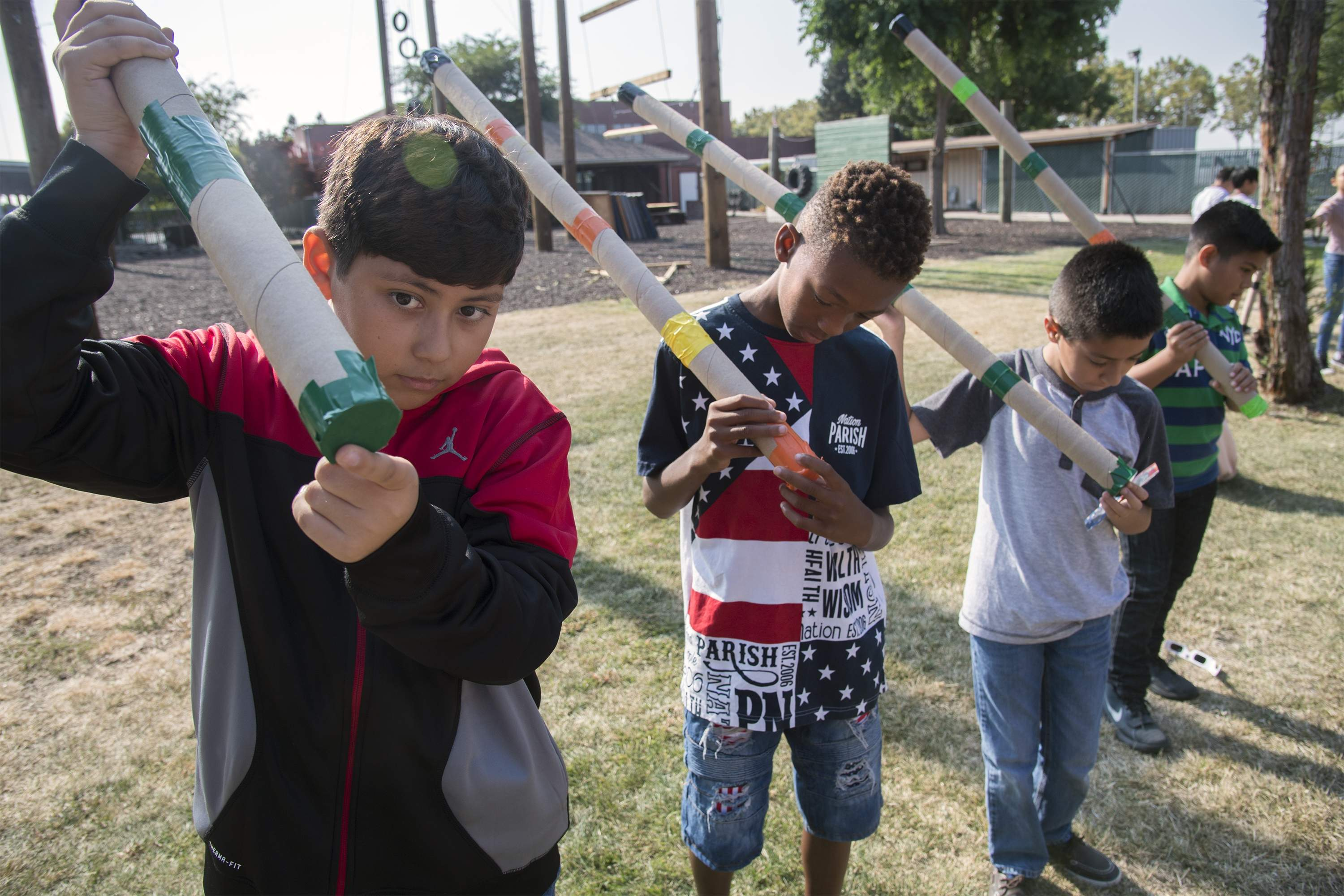 Luis Ramirez, 11, left, Kurtis Vickers, 10, Fabian Mena, 10, and Diego Caballero,10, look at the partial eclipse through homemade pinhole viewers at the San Joaquin County Office of Education in Stockton. [CLIFFORD OTO/THE RECORD]