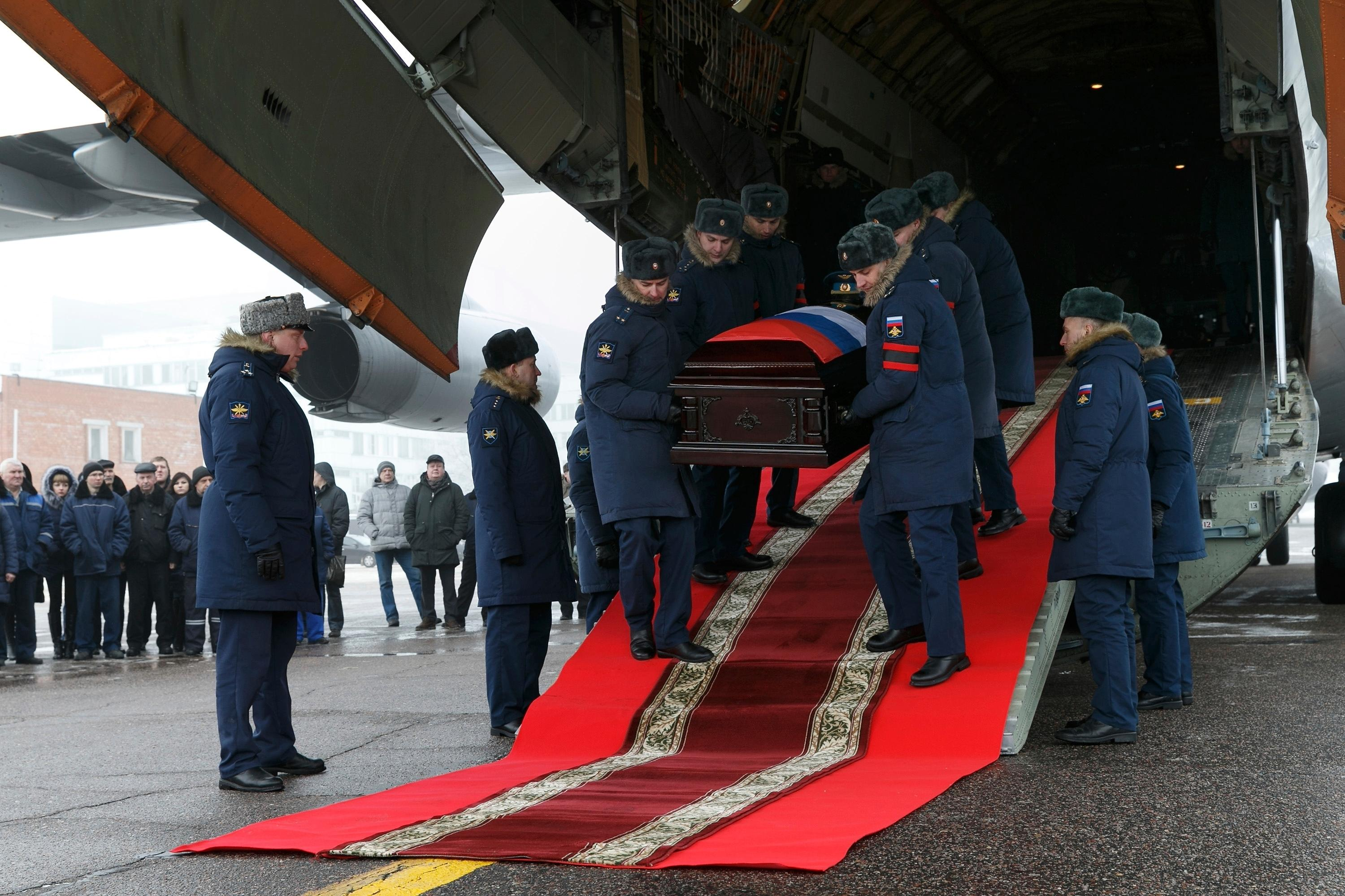 Russian officers carry out from a plane a coffin with the body of Russian Roman Filipov, the pilot of the Su-25 jet who ejected after Syrian insurgents shot down his plane traded fire with militants on the ground and then blew himself up to avoid being captured, during a funeral service in Voronezh, Russia, Thursday, Feb. 8, 2018. (Vadim Savitsky/Pool Photo via AP)
