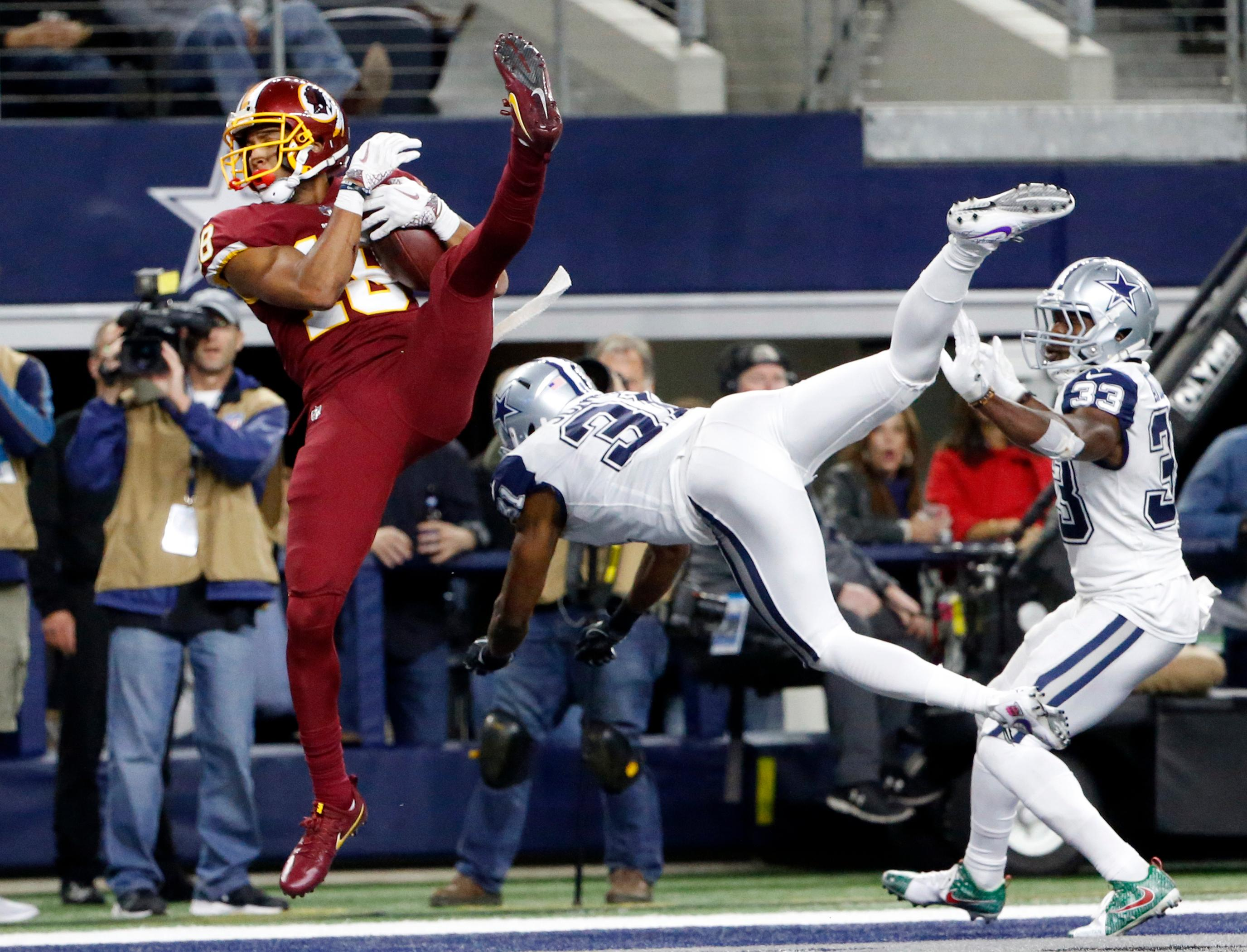 Washington Redskins' Josh Doctson (18) comes down with a touchdown catch in front of Dallas Cowboys safety Byron Jones (31) and Chidobe Awuzie (33) in the second half of an NFL football game, Thursday, Nov. 30, 2017, in Arlington, Texas. (AP Photo/Michael Ainsworth)