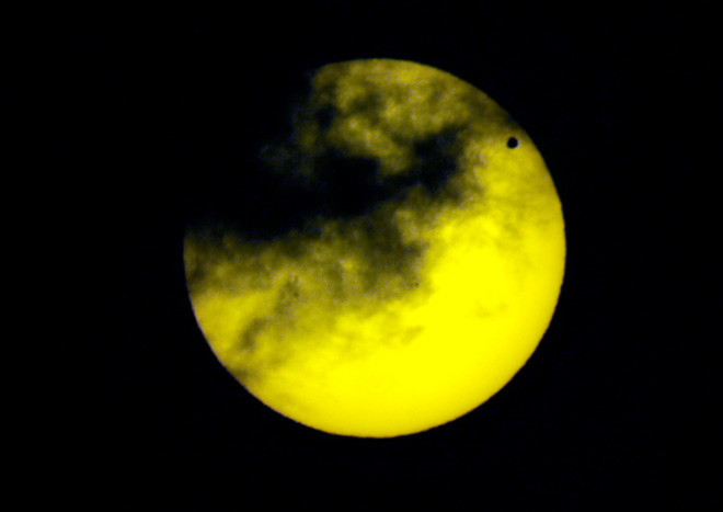 Venus, upper right, transits the sun as seen through a dark glass from Quito, Ecuador, Tuesday, June 5, 2012.