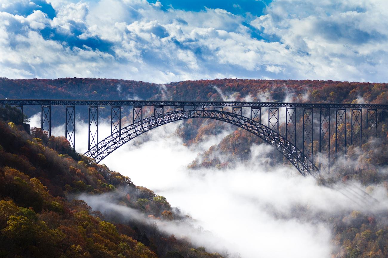 PLACE: New River Gorge Bridge in West Virginia / DISTANCE: 257 miles southeast of Cincinnati, a four-and-a-half-hour drive / Set within a palette of fall colors, the New River Gorge Bridge in Victor, West Virginia hangs 876 feet above the river below and provides contrast to the bucolic view. / Image courtesy of Adventures on the Gorge // Published: 10.19.19