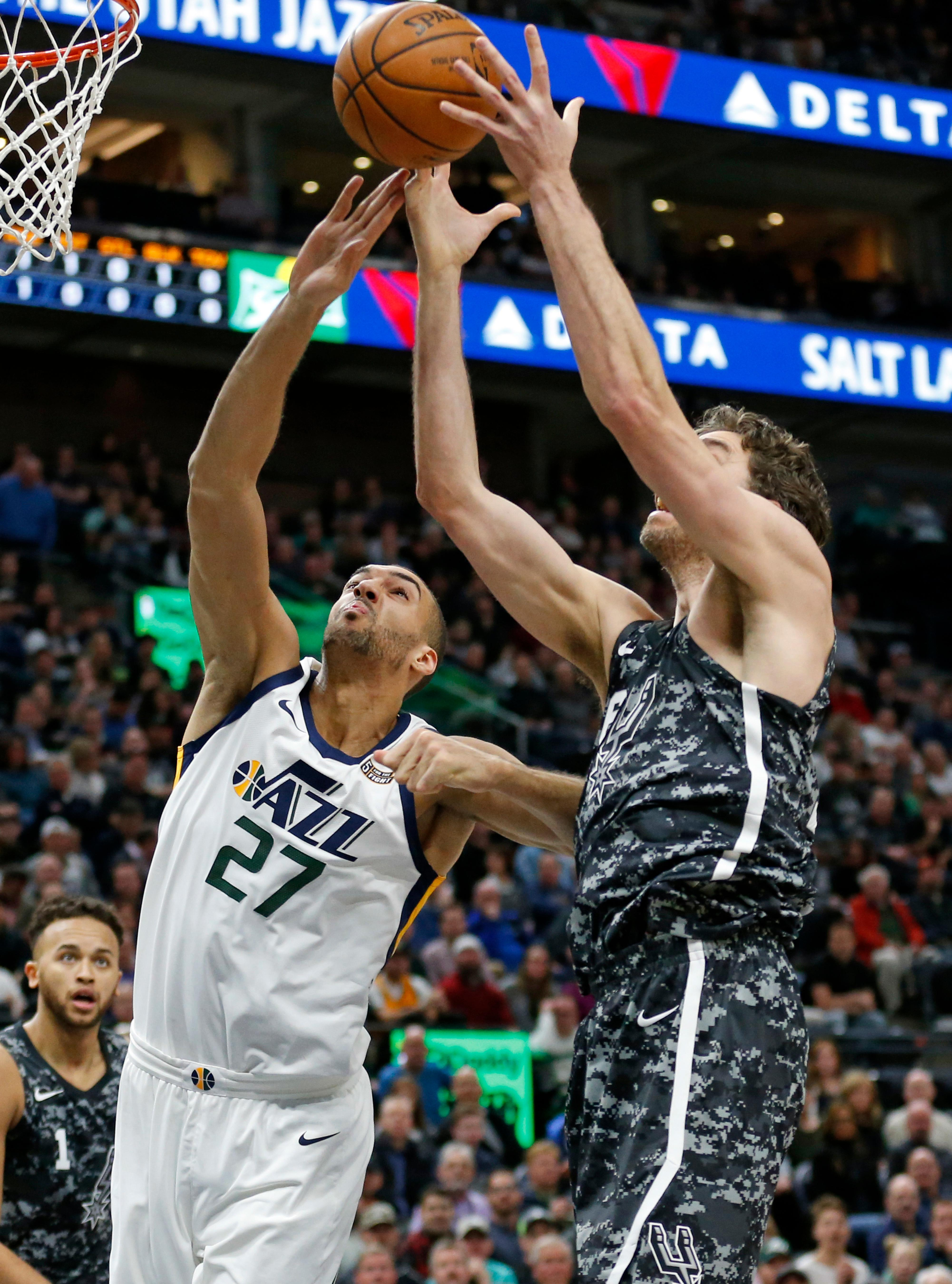 Utah Jazz center Rudy Gobert (27) and San Antonio Spurs center Pau Gasol, right, reach for a rebound in the first half during an NBA basketball game Monday, Feb. 12, 2018, in Salt Lake City. (AP Photo/Rick Bowmer)