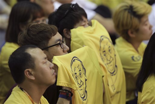 Young participants holding t-shirts bearing the image of Pope Francis listen to Francis giving a speech during a meeting with Asian youth in South Korea.