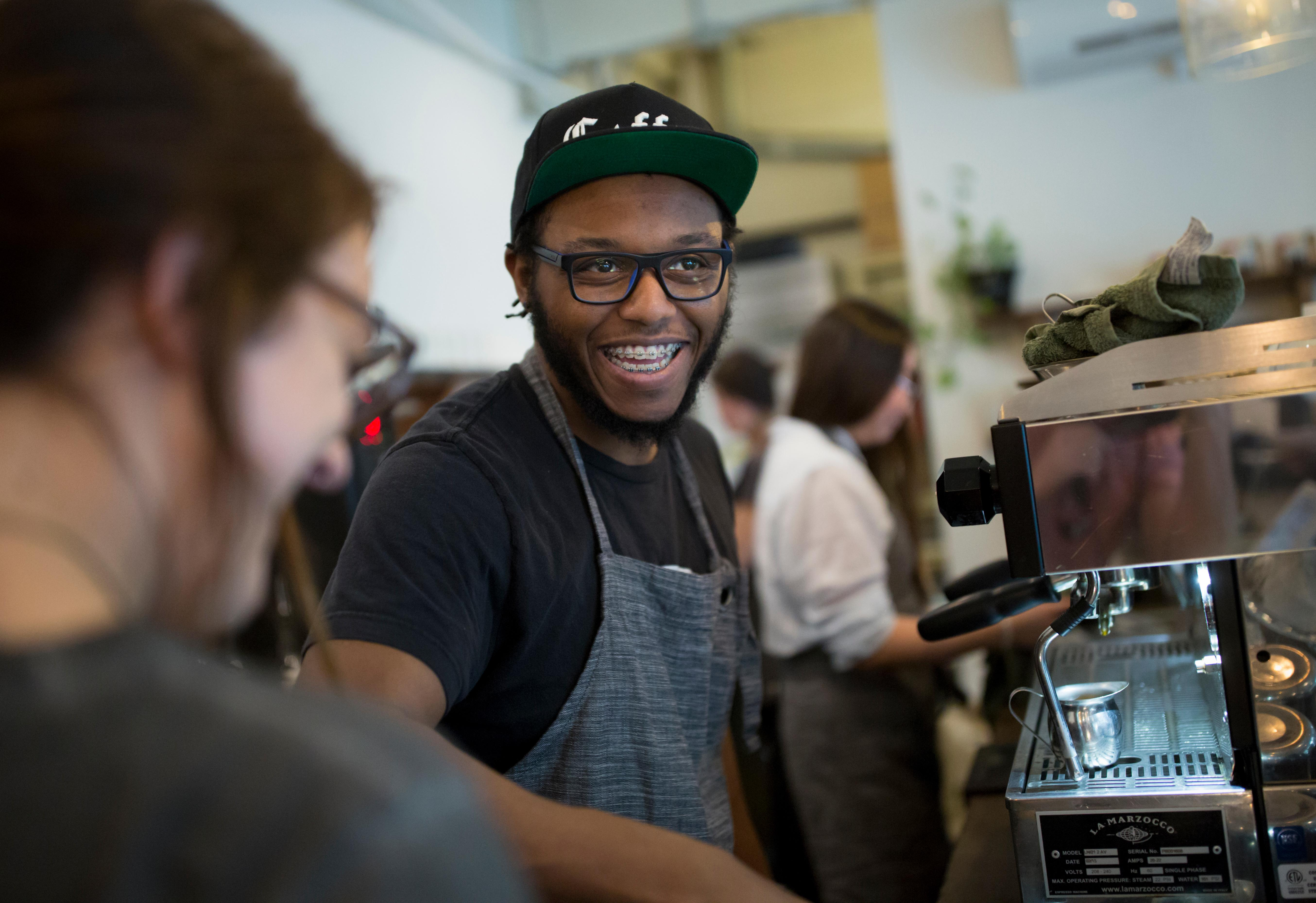 Shift Supervisor Anthony Harris laughs with a coworker as he pours a cup of coffee at Street Bean Coffee Roasters, a local coffee shop and non-profit that's dedicated to providing work opportunities for street-involved youth. Harris graduated from the roaster's apprenticeship program, and is now working full time. (Sy Bean / Seattle Refined)