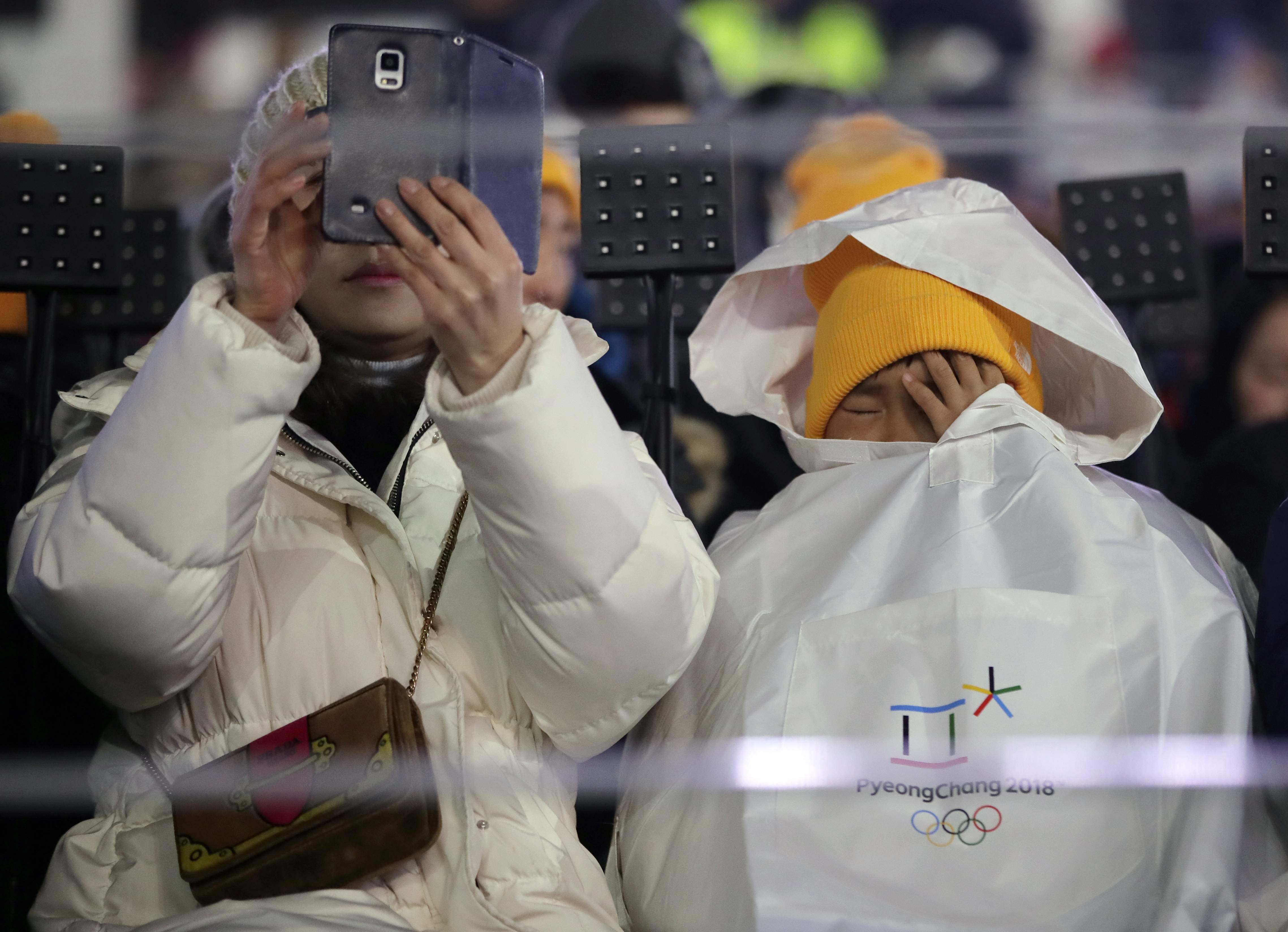 A young spectator, right, tries to keep warm during the opening ceremony of the 2018 Winter Olympics in Pyeongchang, South Korea, Friday, Feb. 9, 2018. (AP Photo/Vadim Ghirda)