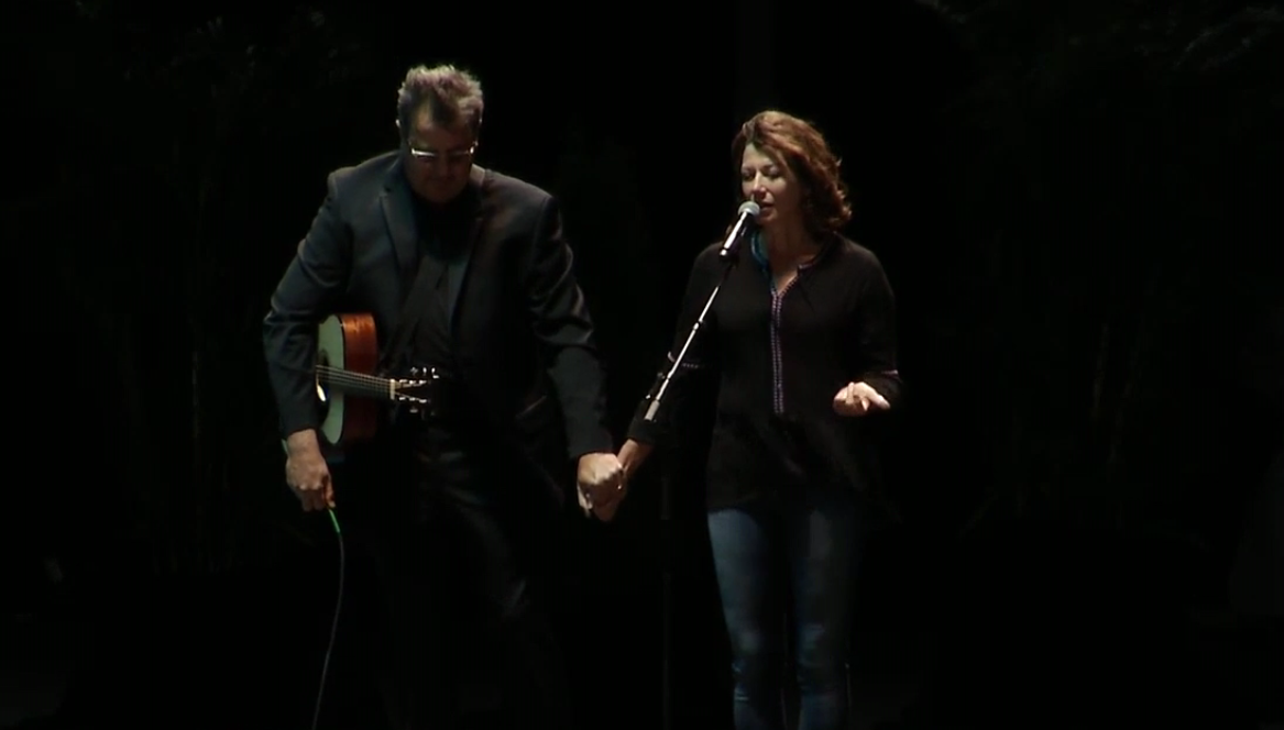 Amy Grant joins hands with Vince Gill to lead the crowd in prayer at a vigil following the mass shooting in Las Vegas on Sunday night. (WZTV)<p></p>