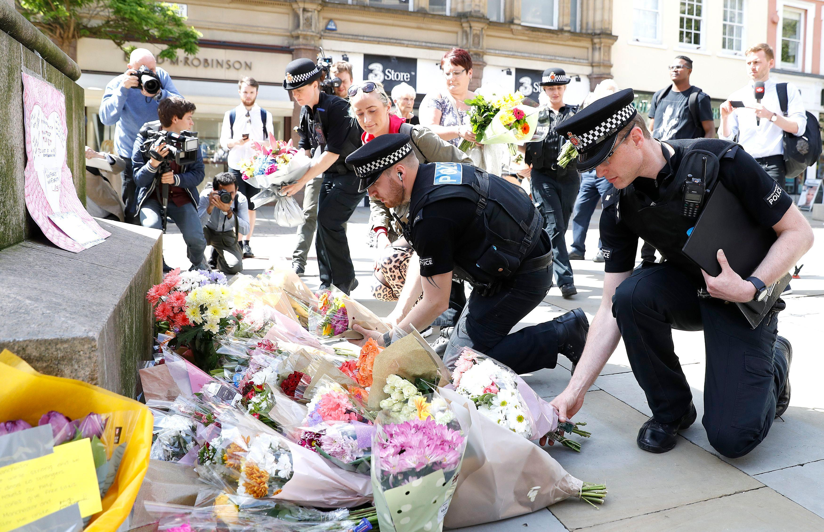 Police offices add to the flowers for the victims of Monday night pop concert explosion, in St Ann's Square, Manchester,  Tuesday May 23, 2017. ( Martin Rickett/PA via AP)