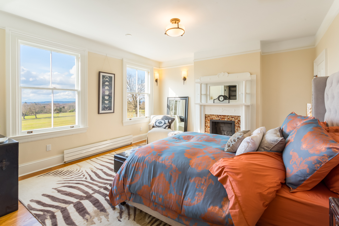 The master bedroom of the Frederick is located on the second floor and features expansive views, original flooring and fireplace, plus a fully renovated Master bathroom.