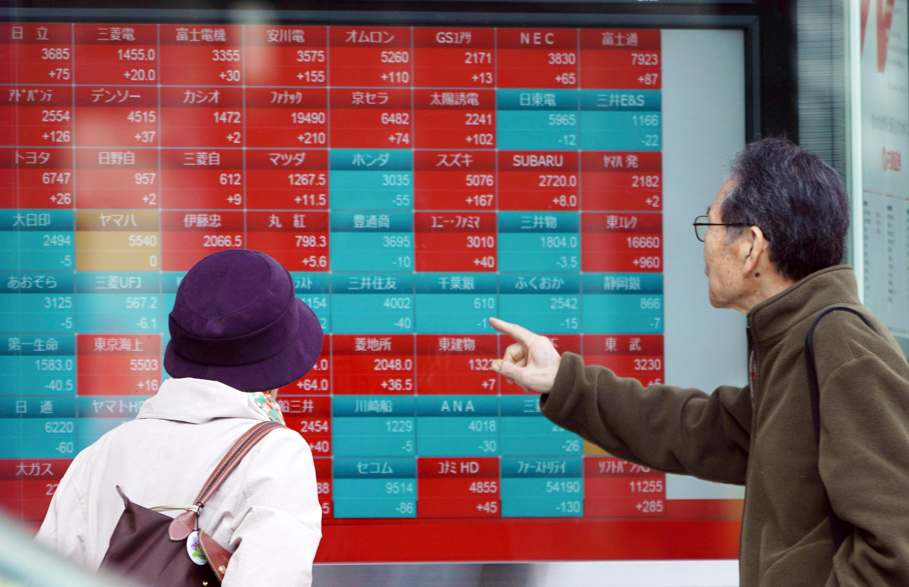 A man and a woman look at an electronic stock board showing Japan's Nikkei 225 index at a securities firm in Tokyo Friday, March 22, 2019.{ } (AP Photo/Eugene Hoshiko)