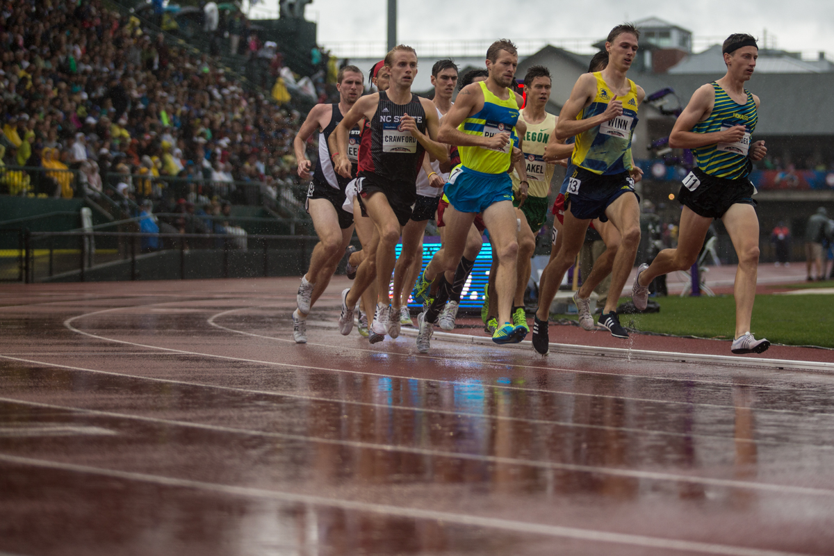 Men in the 1500m battle the elements while coming around the first curve of the track. Photo by Dillon Vibes