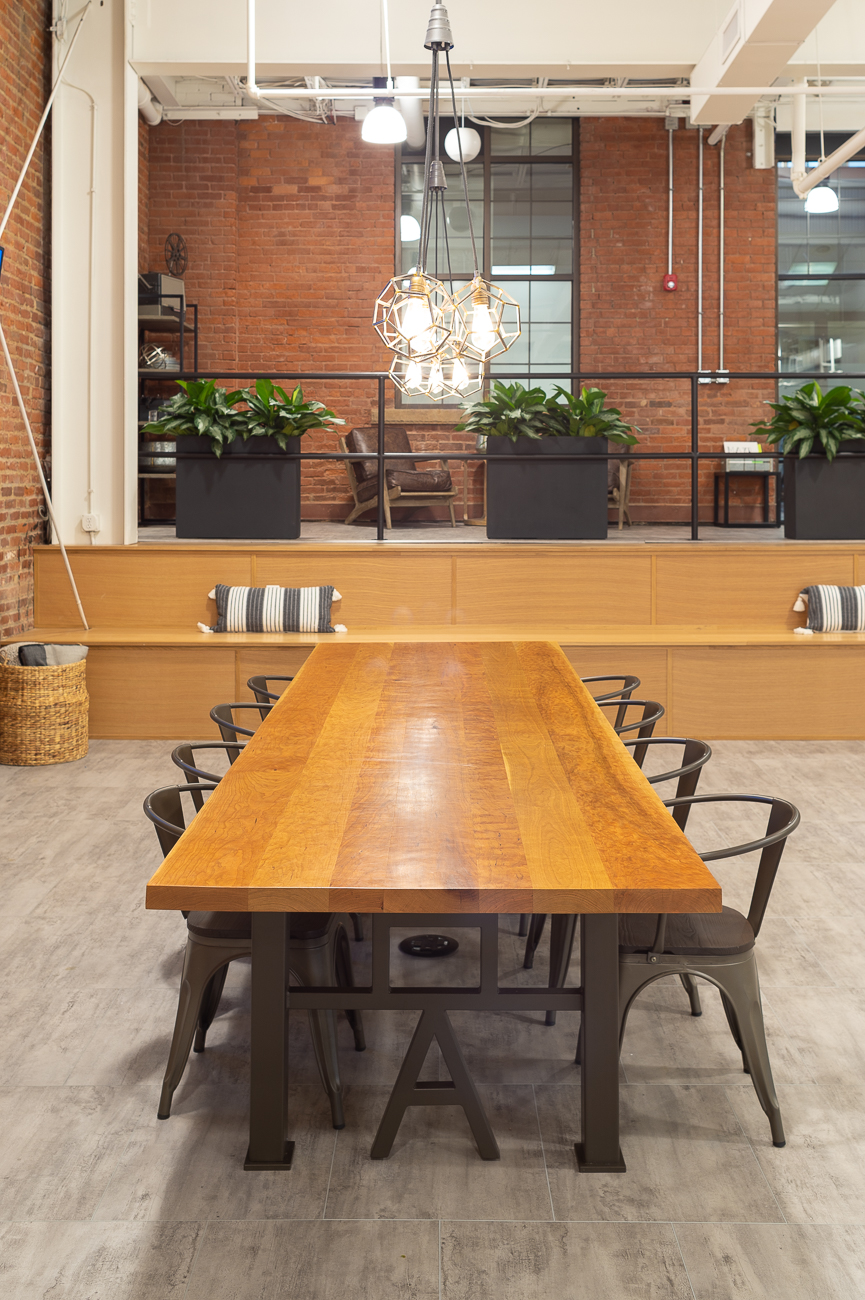 There's no formal conference room. The middle space is used for their office meetings and as a collaborative space. Scott Berkley, a carpenter for the Cincinnati Ballet, designed the custom cherry wood table and incorporated the agency's logo into its support structure. The table is a visual focal point of the room. / Image: Phil Armstrong, Cincinnati Refined // Published: 3.22.19