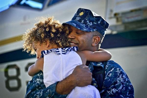 Navy Lt. Cmdr. Charles Harris embraces his daughter during a homecoming celebration at Naval Air Station North Island in San Diego, Aug. 7, 2013.
