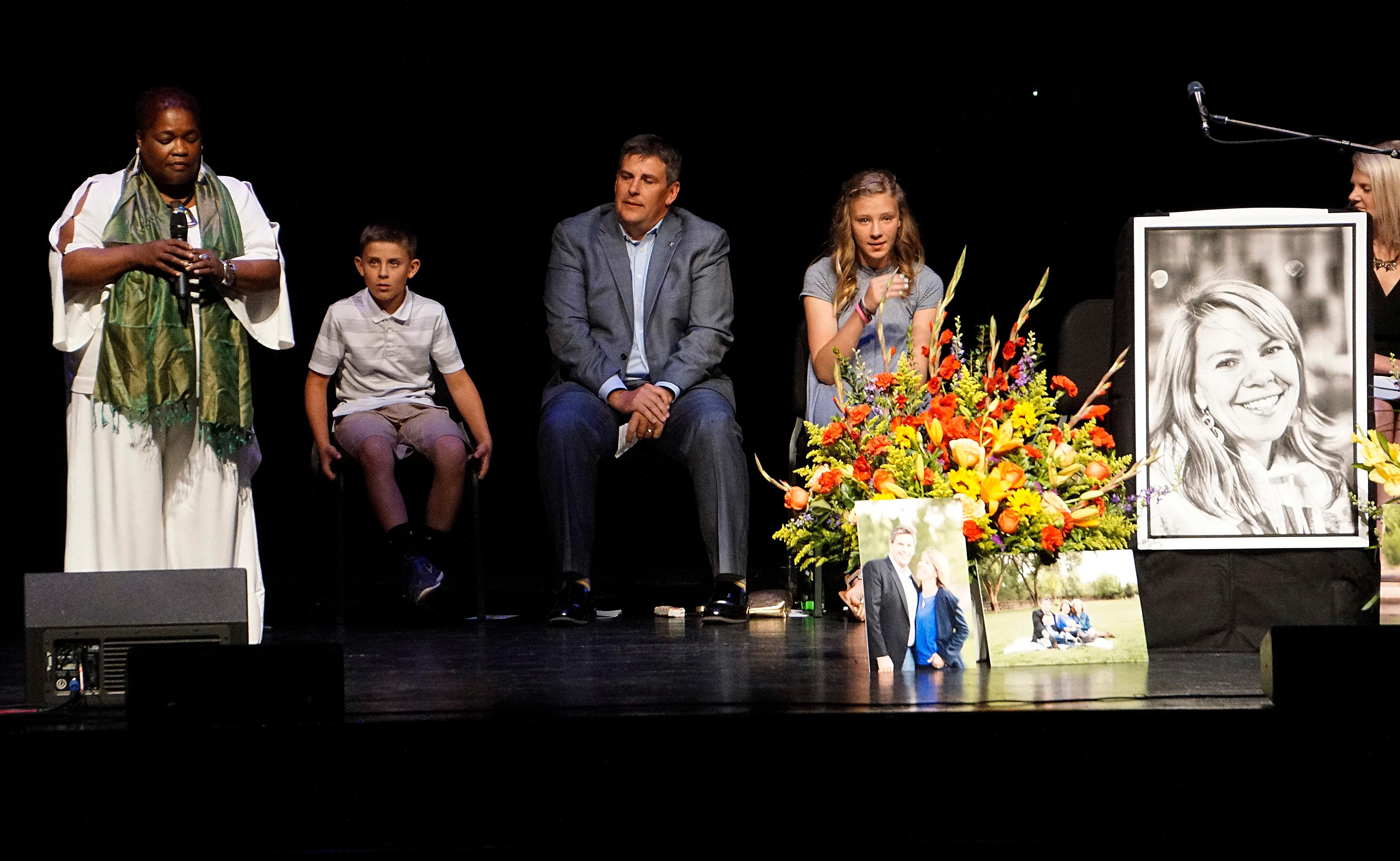 Cathryn McGill, standing, performs a song at a memorial service for Michael Riordan's wife Jennifer, who died on Tuesday in the Southwest Airlines flight 1380 accident, at Popejoy Hall on the campus of the University of New Mexico in Albuquerque, N.M., Sunday, April 22, 2018. From second left are Jennifer's son, Joshua, husband, Michael and daughter Avrie Riordan. (Adolphe Pierre-Louis/The Albuquerque Journal via AP)