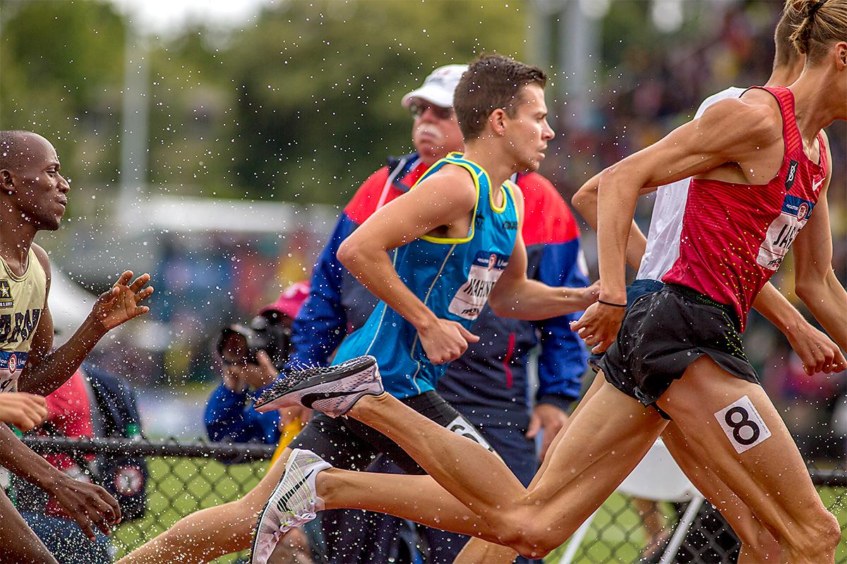 The feet of athletes in the 3,000 meter steeplechase kick up water as they exit the water pit. Photo by August Frank, Oregon News Lab